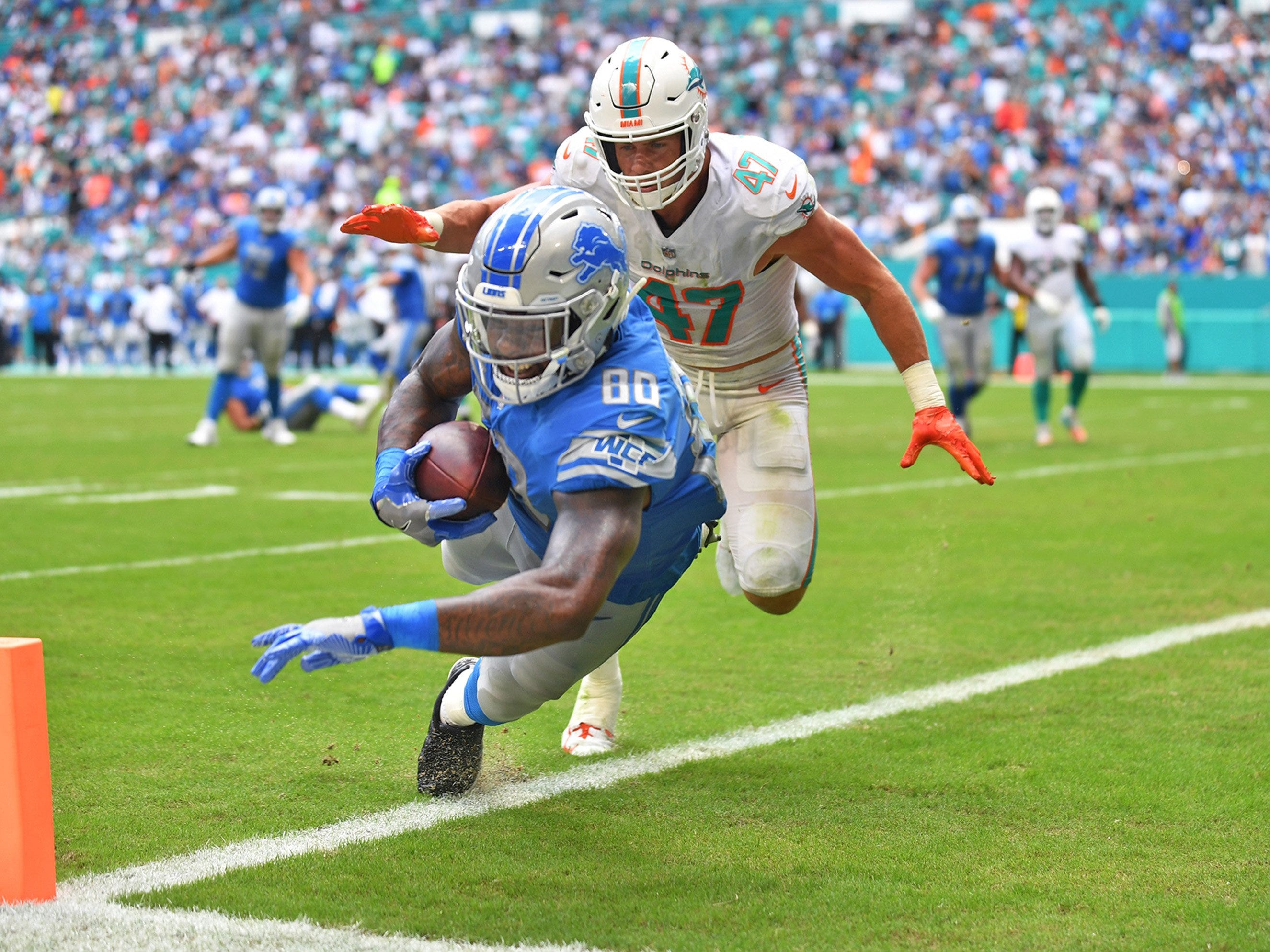 Lions tight end Michael Roberts scores a touchdown past Dolphins linebacker Kiko Alonso during the Lions' 32-21 win on Sunday, Oct. 21, 2018, in Miami Gardens, Fla.