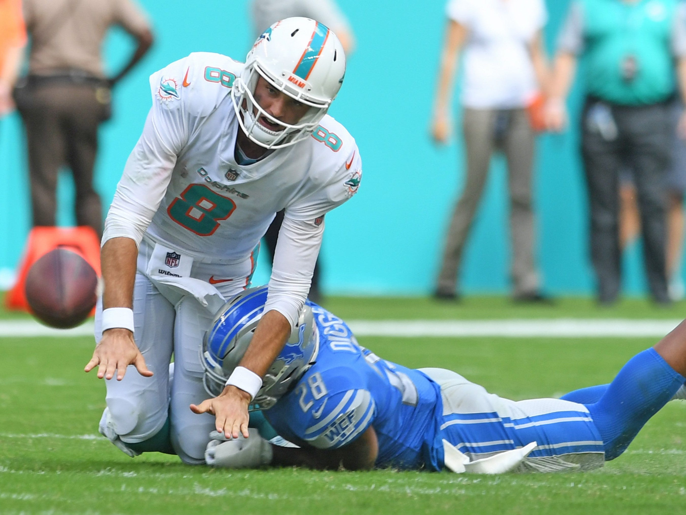 Dolphins quarterback Brock Osweiler throws the ball away before being taken down by Lions strong safety Quandre Diggs in the third quarter of the Lions' 32-21 win on Sunday, Oct. 21, 2018, in Miami Gardens, Fla.