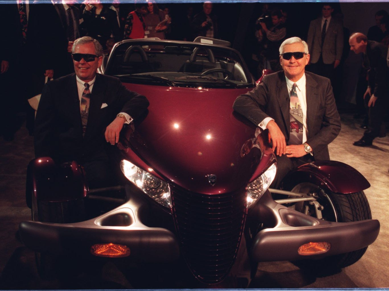 "Bob Eaton (left), President, and Bob Lutz, Chairman of Chrysler pose for the cameras after unveiling the ""Prowler"",  a concept roadster car that is meant to change Plymouth's outdated image to a more ""hip"" one."
