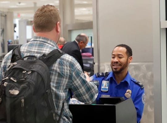 A Transportation Security Administration employee helps air travelers check in at a security checkpoint at Hartsfield Jackson Atlanta International Airport on Monday, Jan. 7, 2019, in Atlanta.