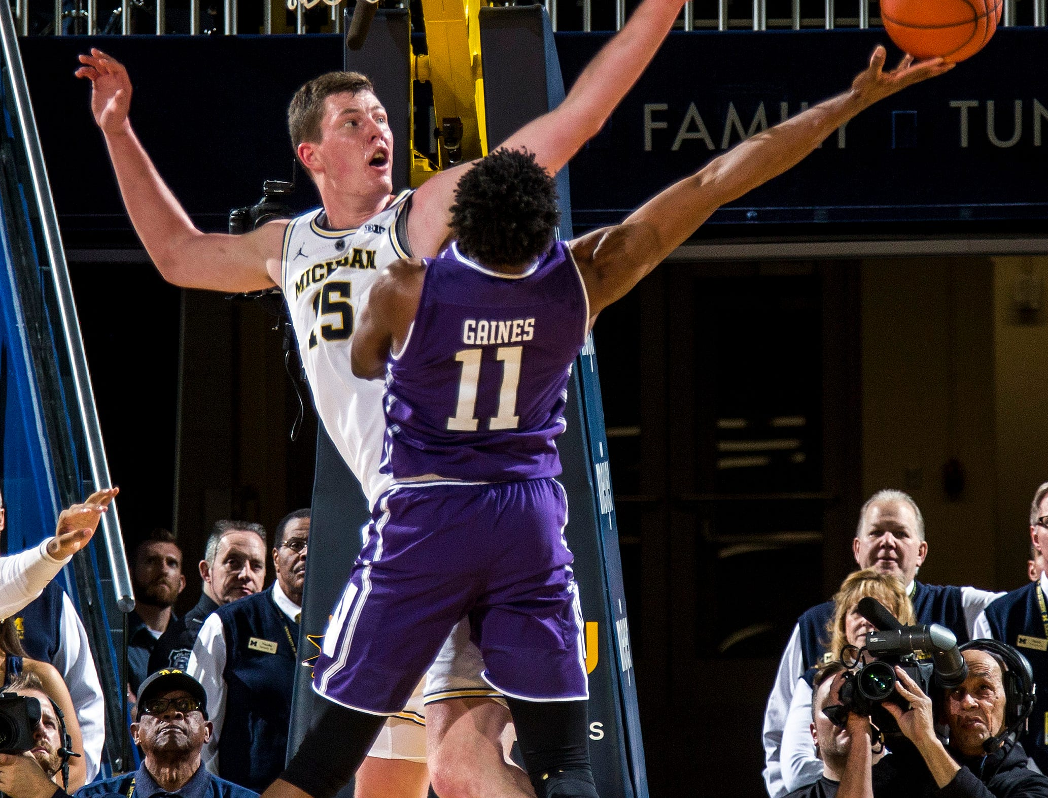 Michigan center Jon Teske, top left, defends the basket from Northwestern guard Anthony Gaines (11) in the second half of an NCAA college basketball game in Ann Arbor, Mich., Sunday, Jan. 13, 2019. Michigan won 80-60. (AP Photo/Tony Ding)