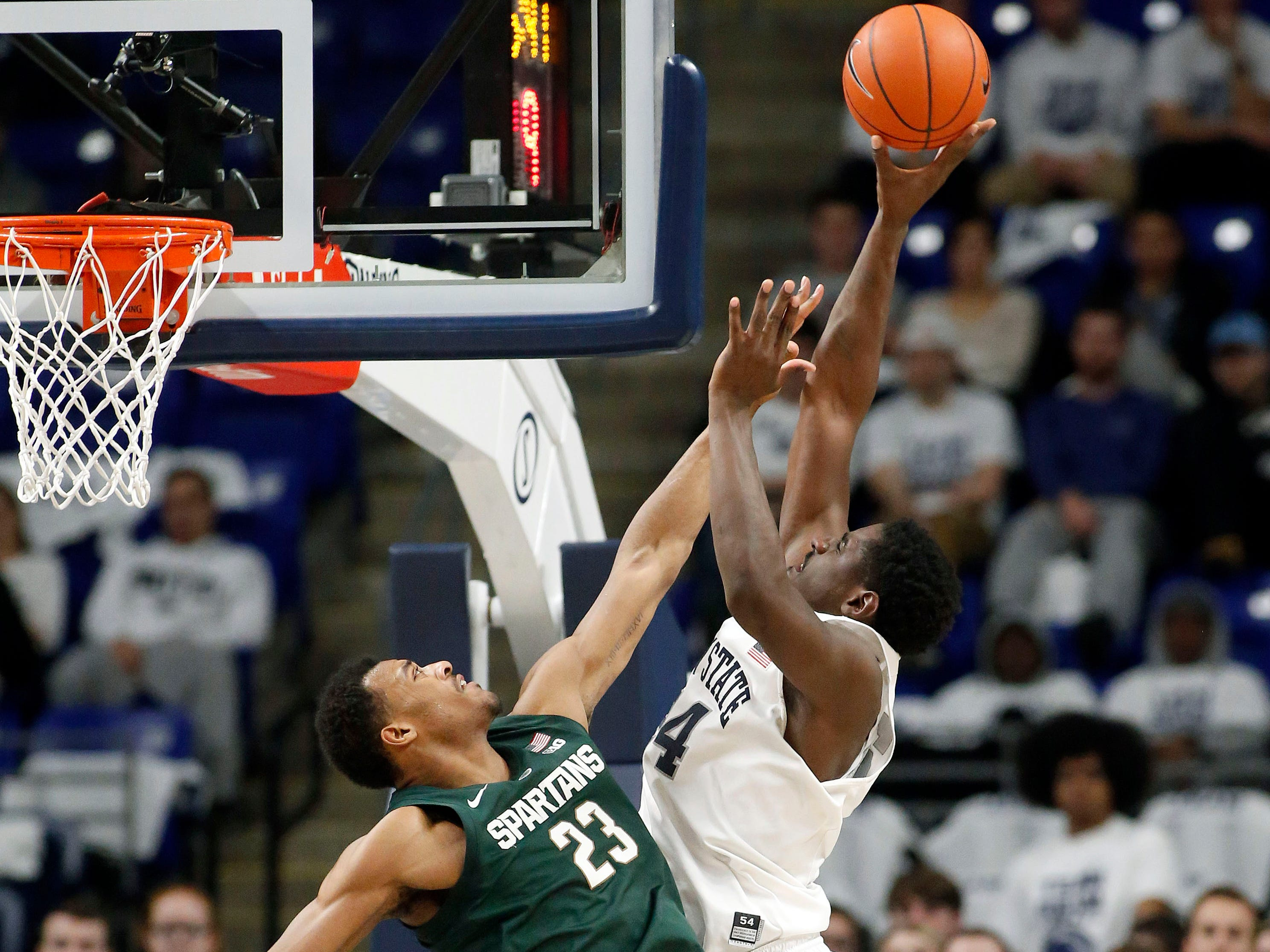 Penn State's Mike Watkins (24) goes to the basket as Michigan State's Xavier Tillman (23) defends during first half action.