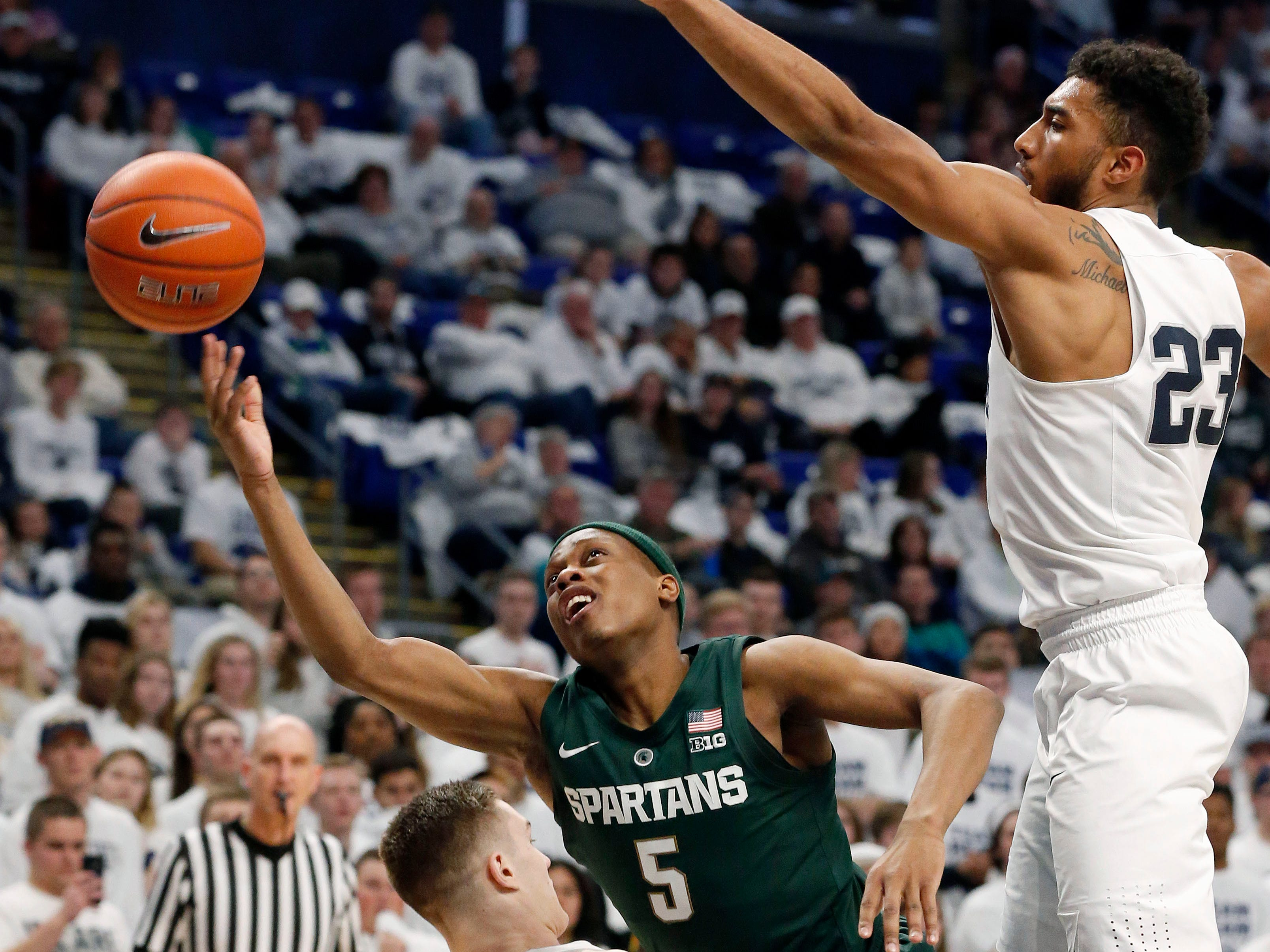 Michigan State's Cassius Winston (5) drives to the hoop as he is fouled by Penn State's Kyle McCloskey (10) during first-half action.