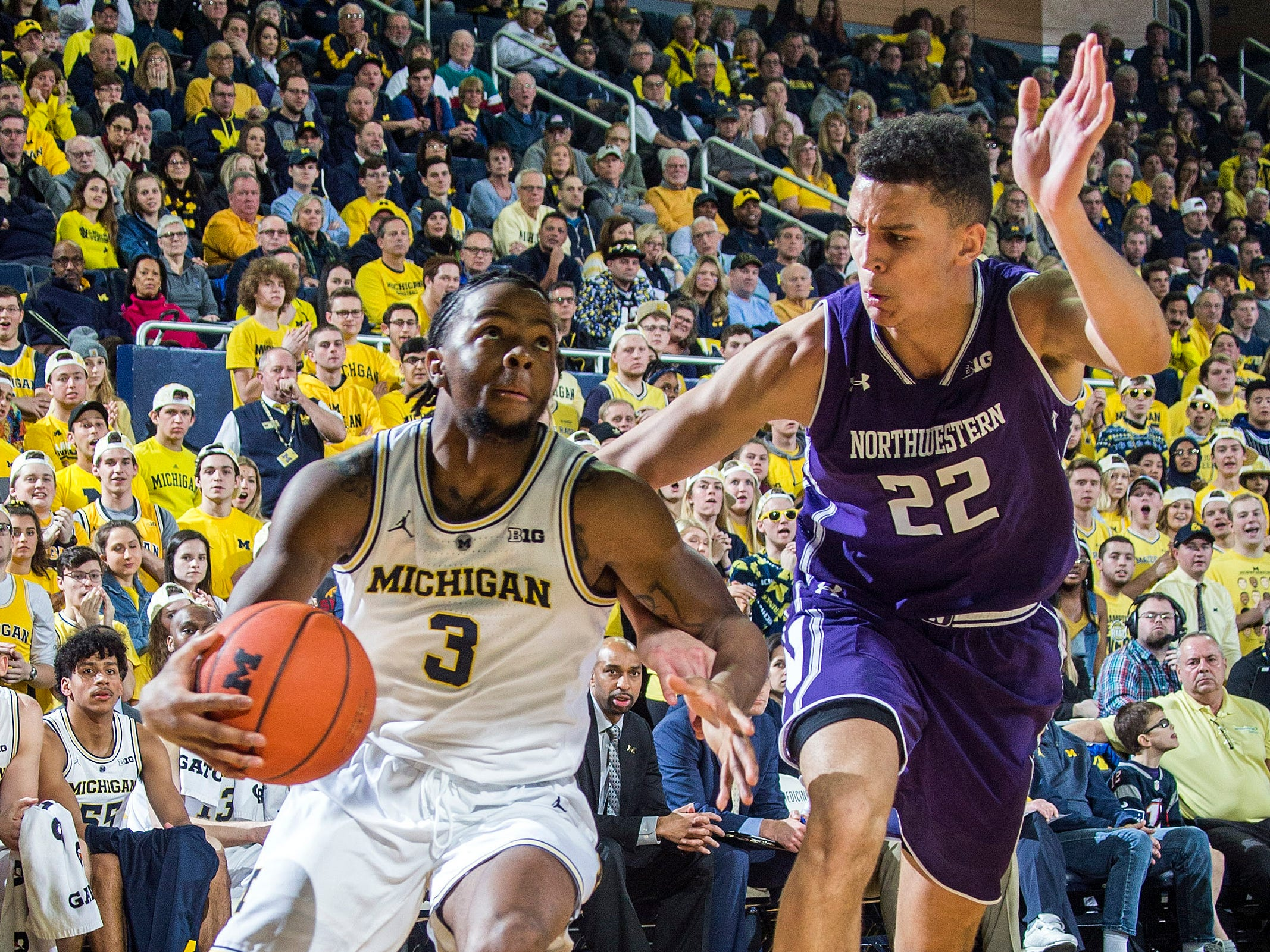 Michigan guard Zavier Simpson (3) drives toward the basket, defended by Northwestern forward Pete Nance (22) in the second half.