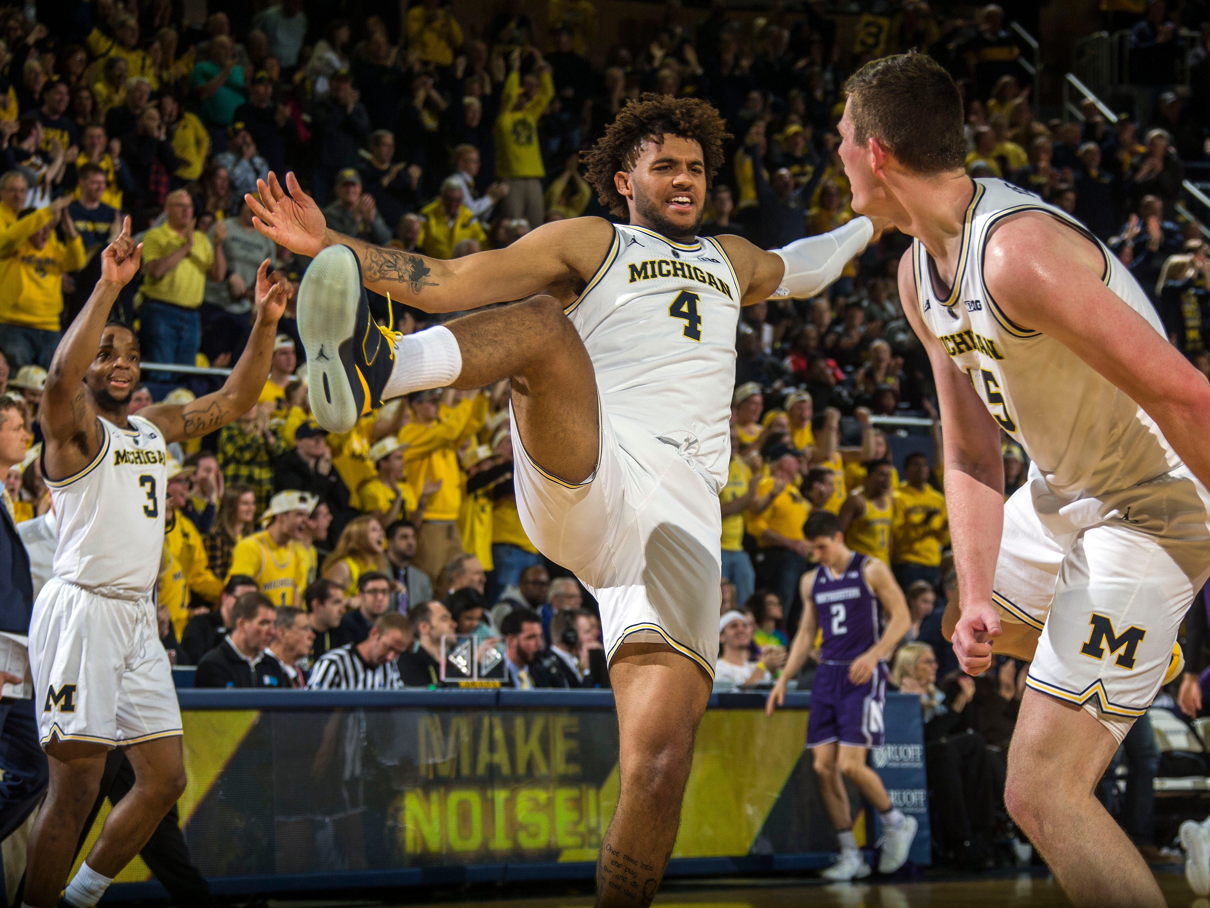 Michigan guard Zavier Simpson (3) and forward Isaiah Livers (4) celebrate with center Jon Teske, right, after Teske made consecutive three-point baskets in the first half.