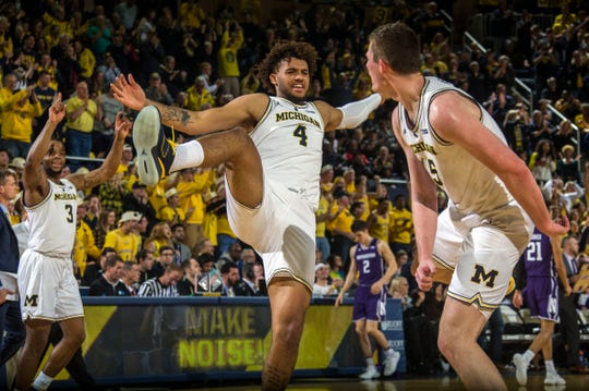 Michigan guard Zavier Simpson (3) and forward Isaiah Livers (4) celebrate with center Jon Teske, right, after Teske made consecutive 3-pointers in the first half