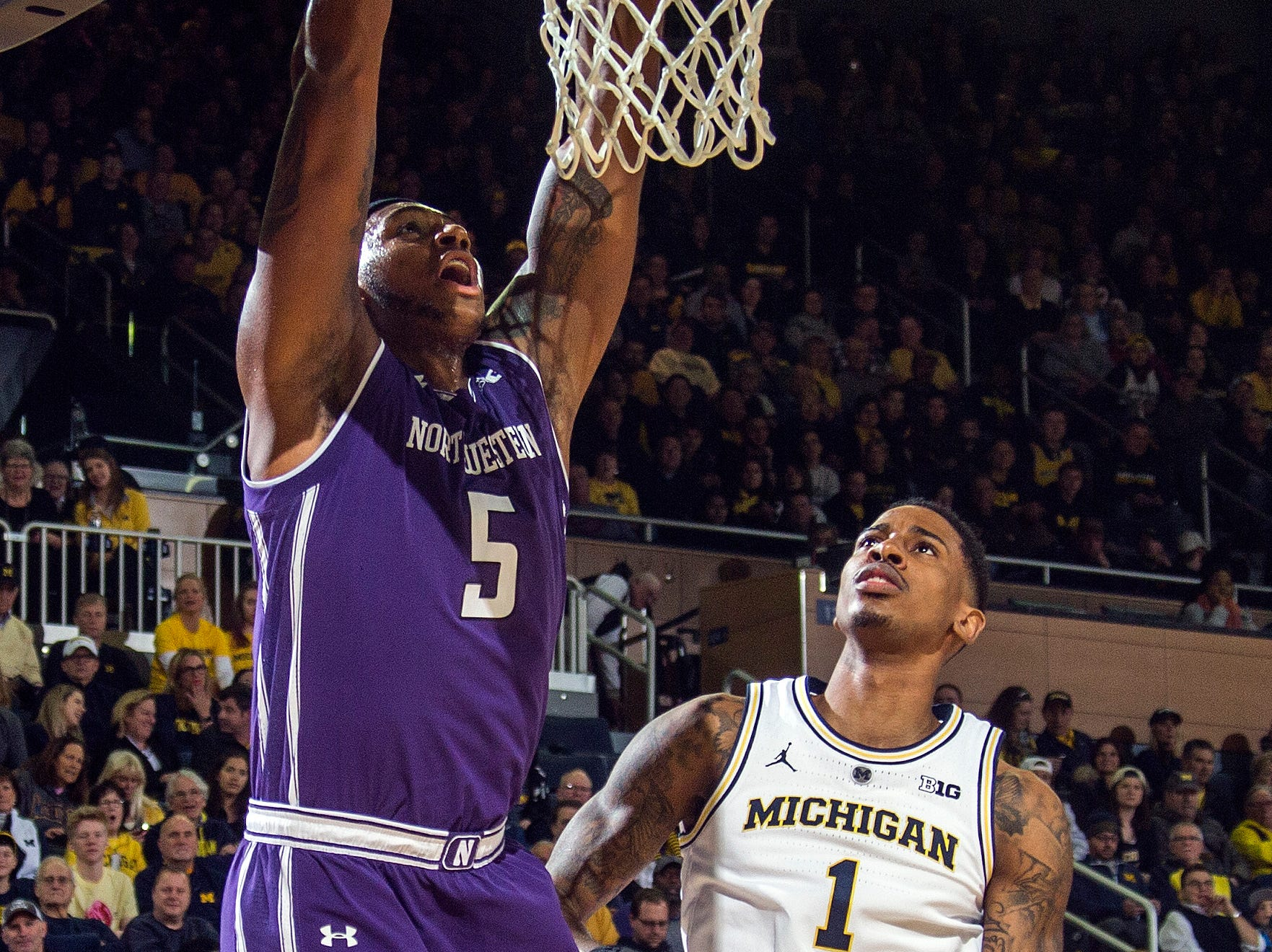 Northwestern center Dererk Pardon (5) dunks next to Michigan guard Charles Matthews (1) in the first half of an NCAA college basketball game at Crisler Center in Ann Arbor, Mich., Sunday, Jan. 13, 2019. (AP Photo/Tony Ding)