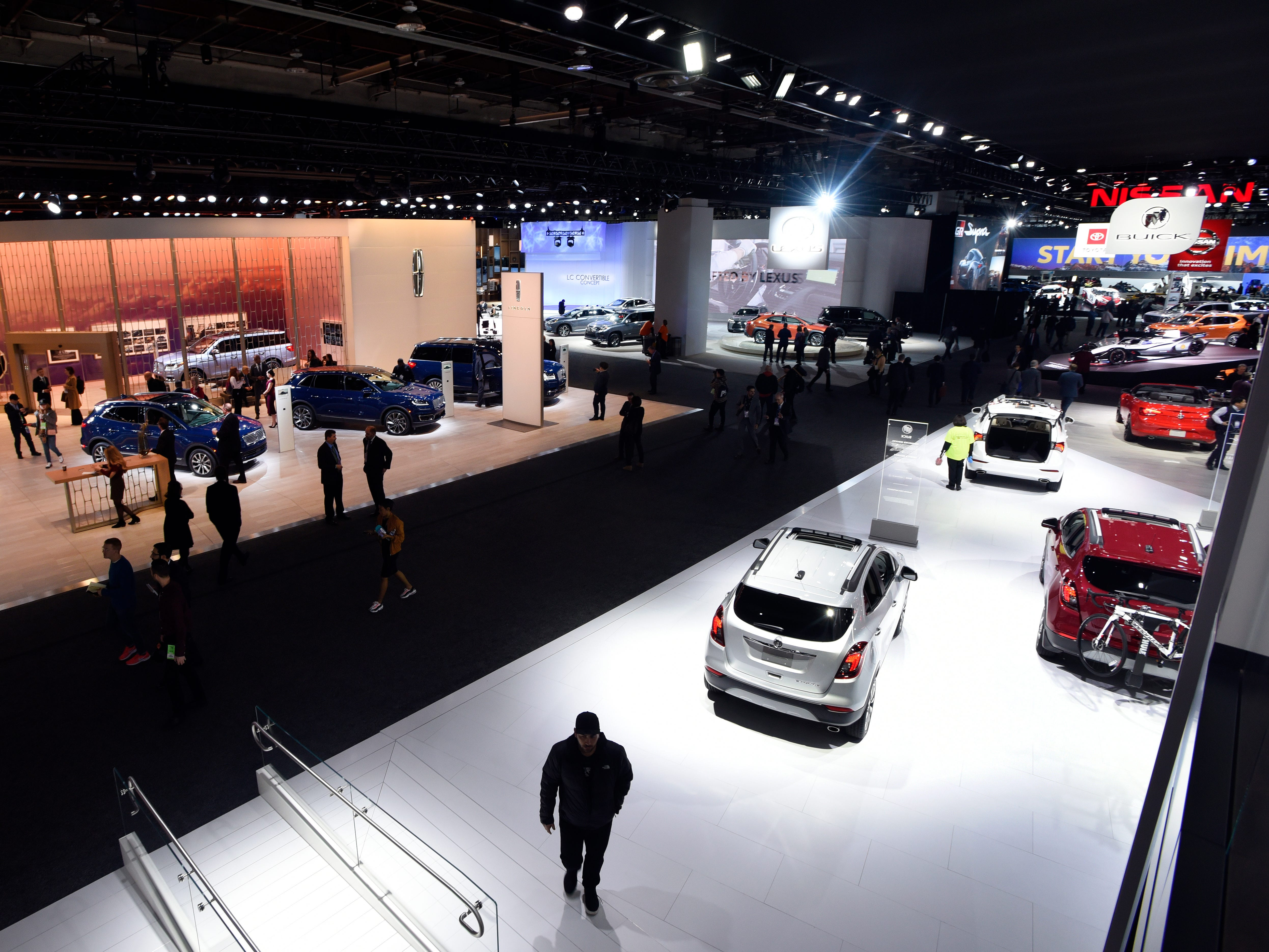 Visitors walk the floor of the North American International Auto Show at Cobo Center in Detroit Monday.