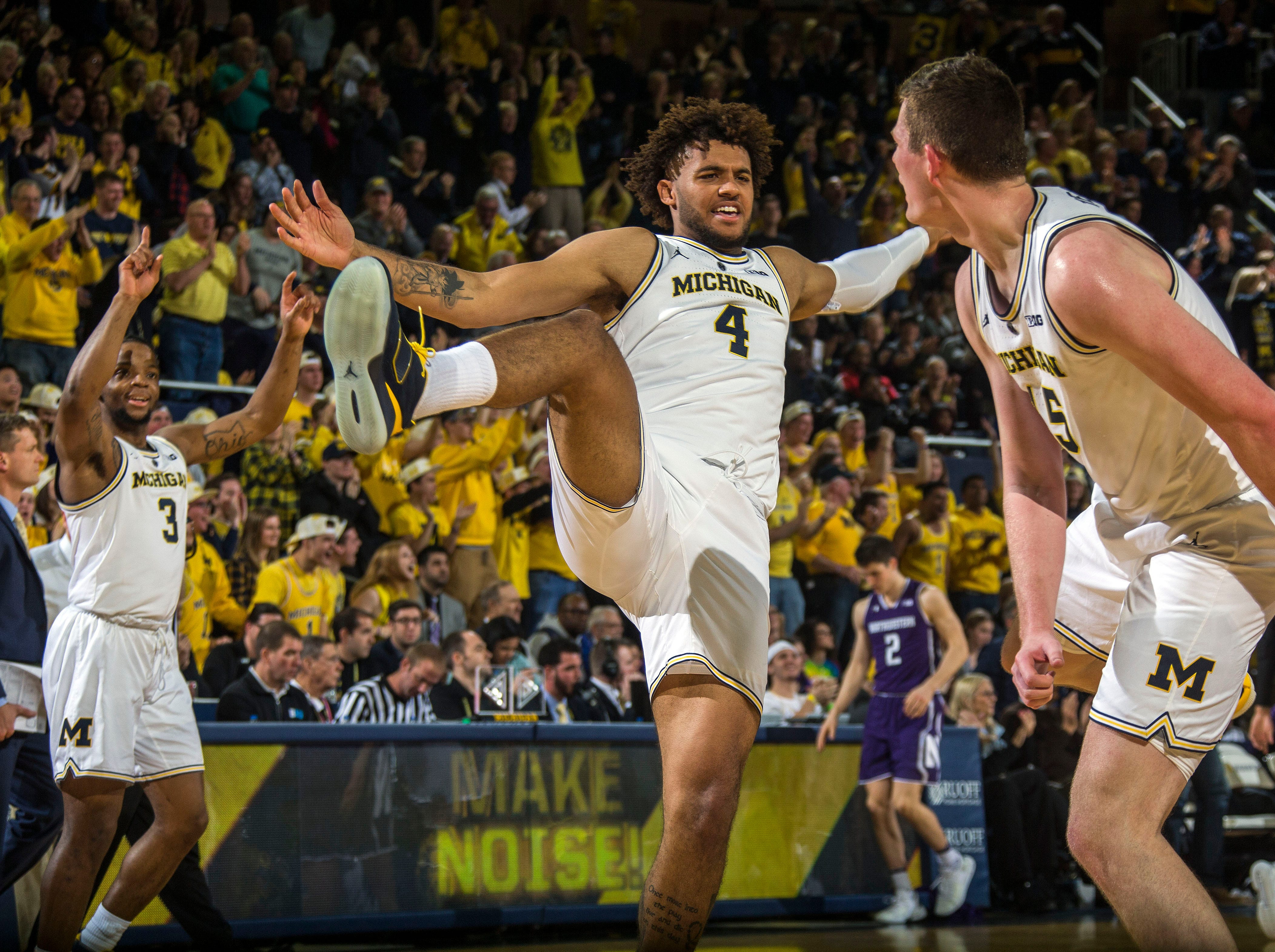 Michigan guard Zavier Simpson (3) and forward Isaiah Livers (4) celebrate with center Jon Teske, right, after Teske made consecutive three-point baskets in the first half of an NCAA college basketball game against Northwestern at Crisler Center in Ann Arbor, Mich., Sunday, Jan. 13, 2019. (AP Photo/Tony Ding)