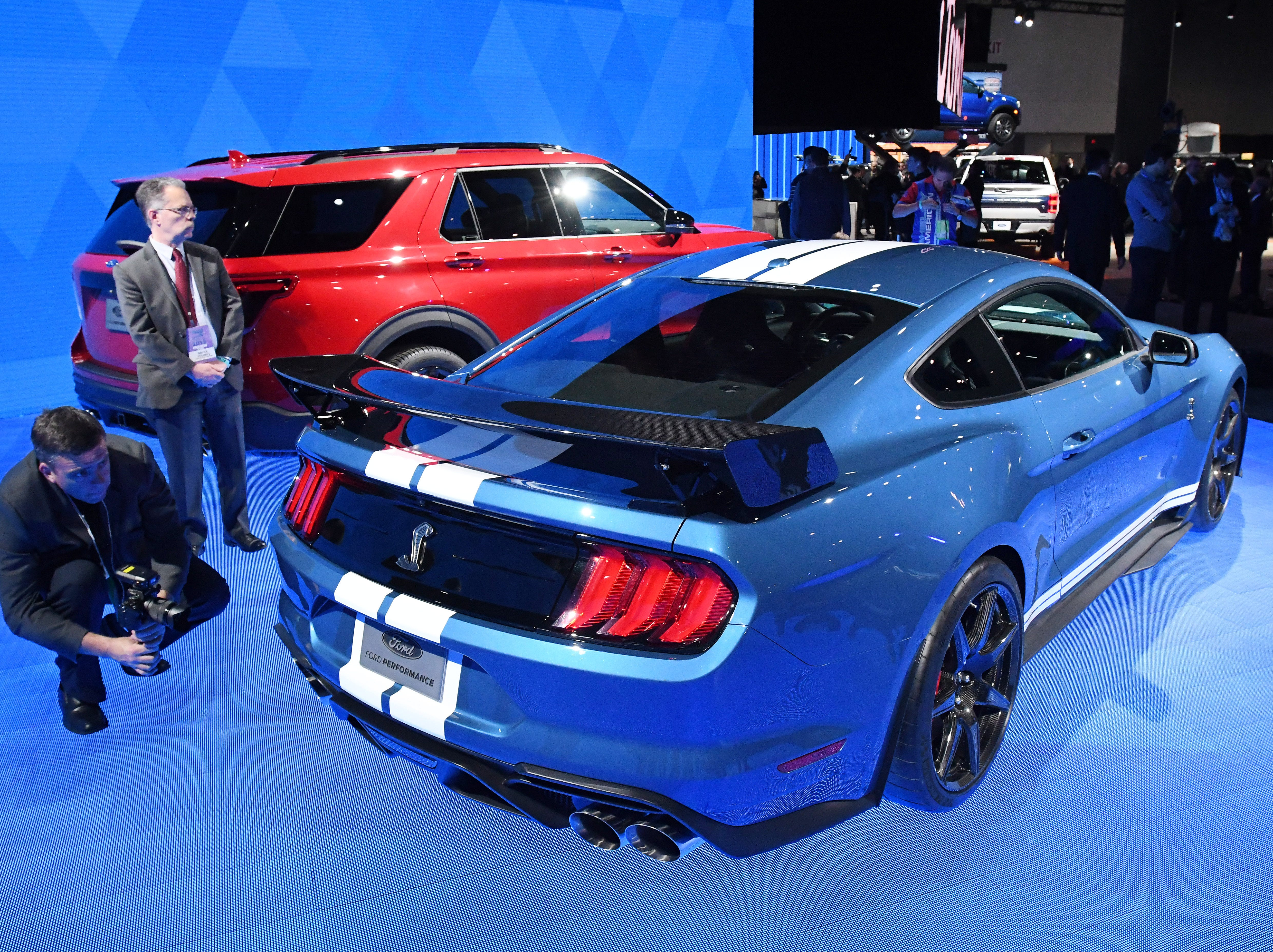 Members of the media look over the Mustang Shelby GT500 and Ford Explorer ST after their unveiling at the Detroit Auto Show.