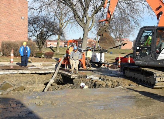 Workers from Lakeshore Global Corporation work on a water main break at Larned and St. Maron Place in Detroit Sunday morning.