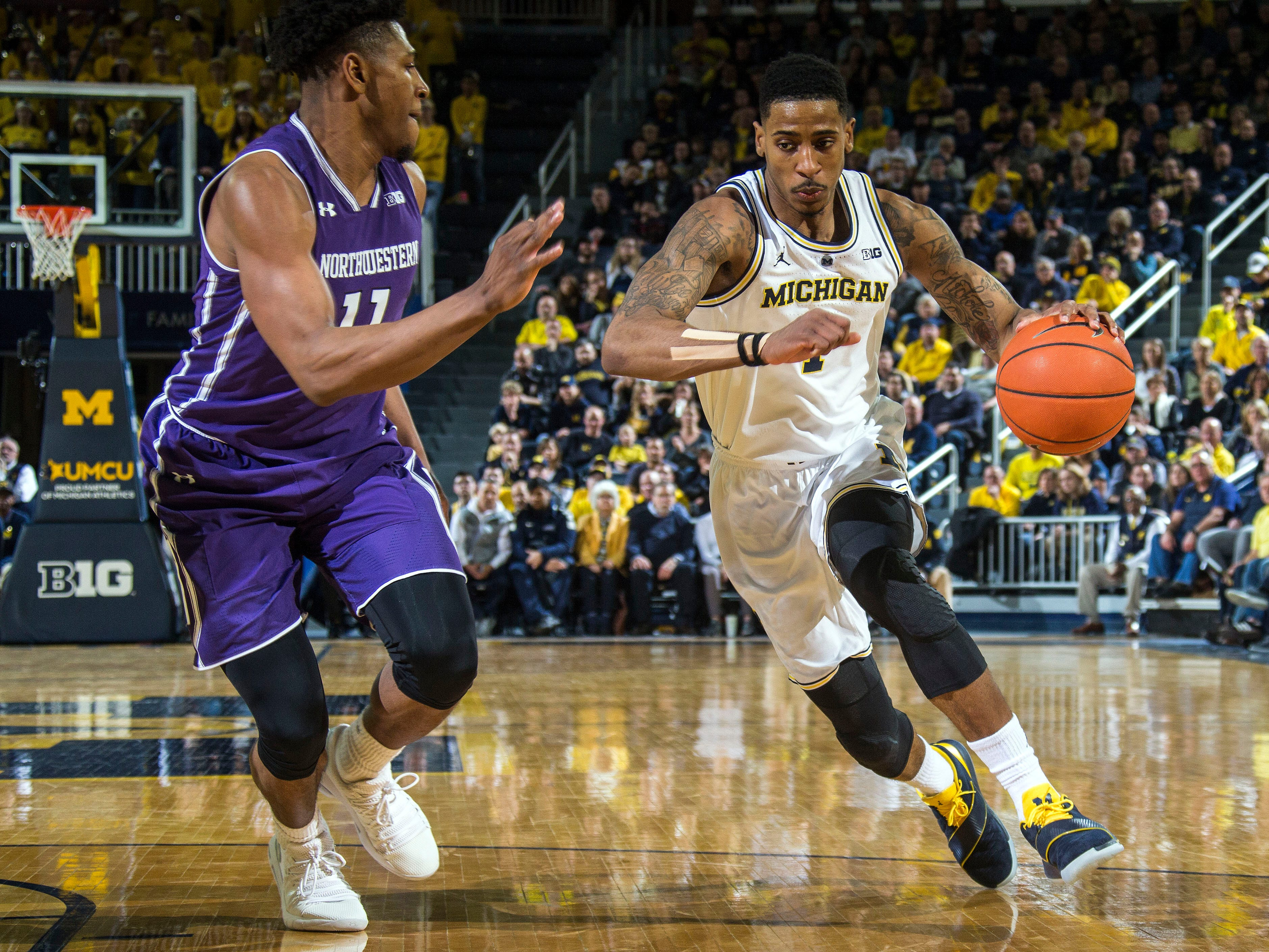 Northwestern guard Anthony Gaines (11) defends Michigan guard Charles Matthews, right, in the second half.