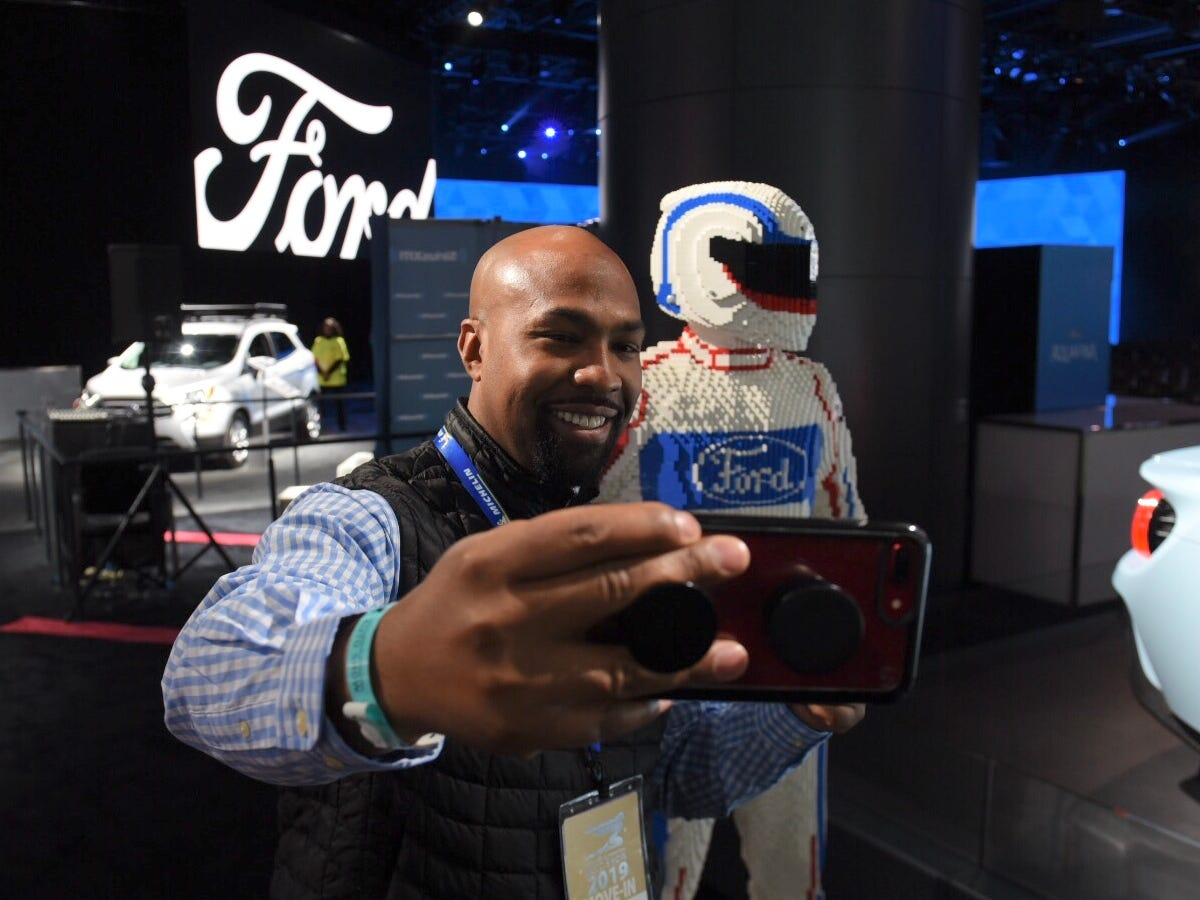Marcus Wilson of Michelin Tire snaps a selfie with a Lego race car driver at the Ford display.