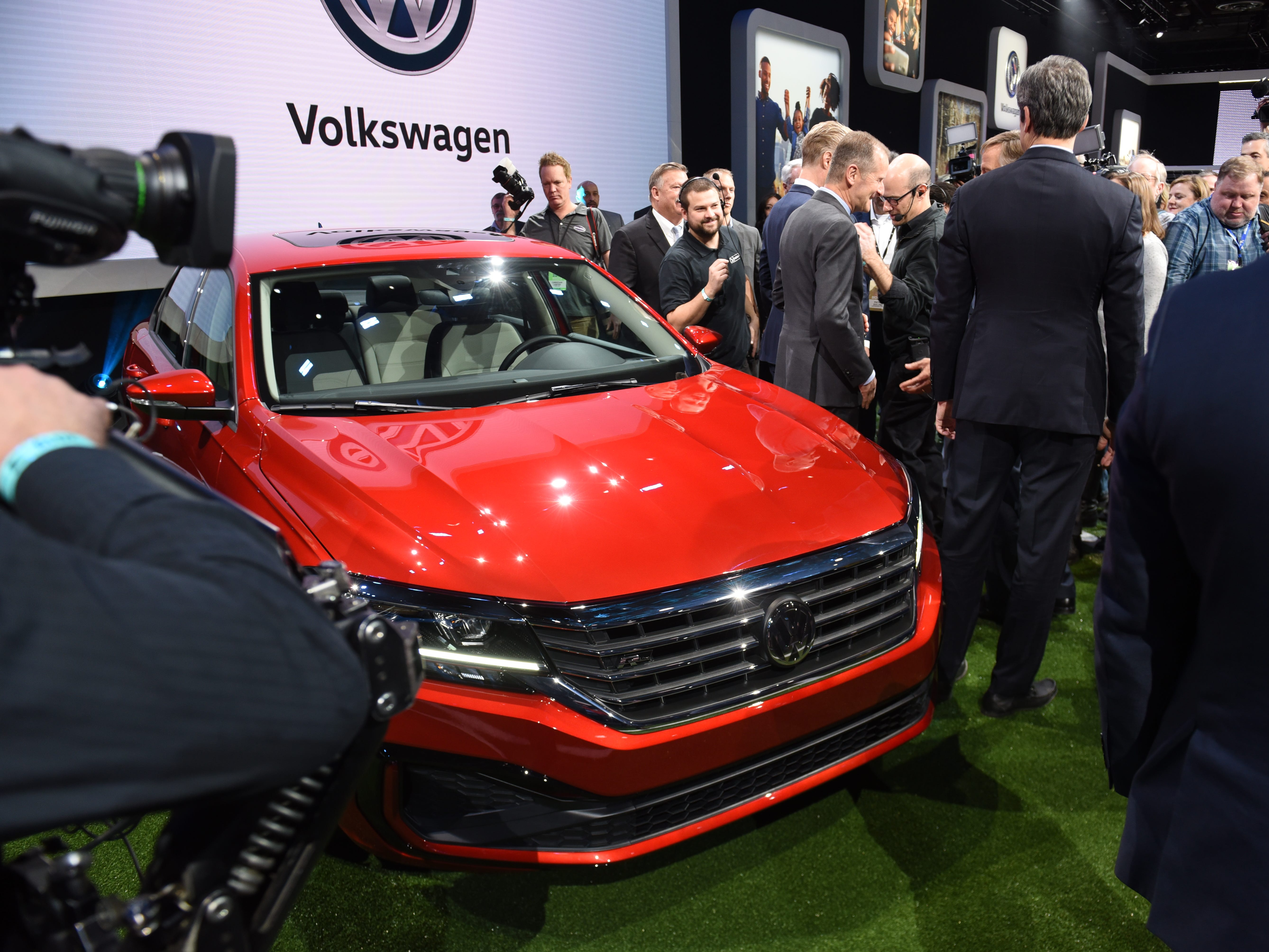 Journalist surround the 2020 Volkswagen Passat after its unveiling.