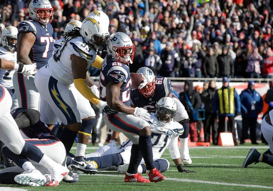 New England Patriots running back Sony Michel scores a touchdown in front of Los Angeles Chargers defensive tackle Darius Philon during the first half.