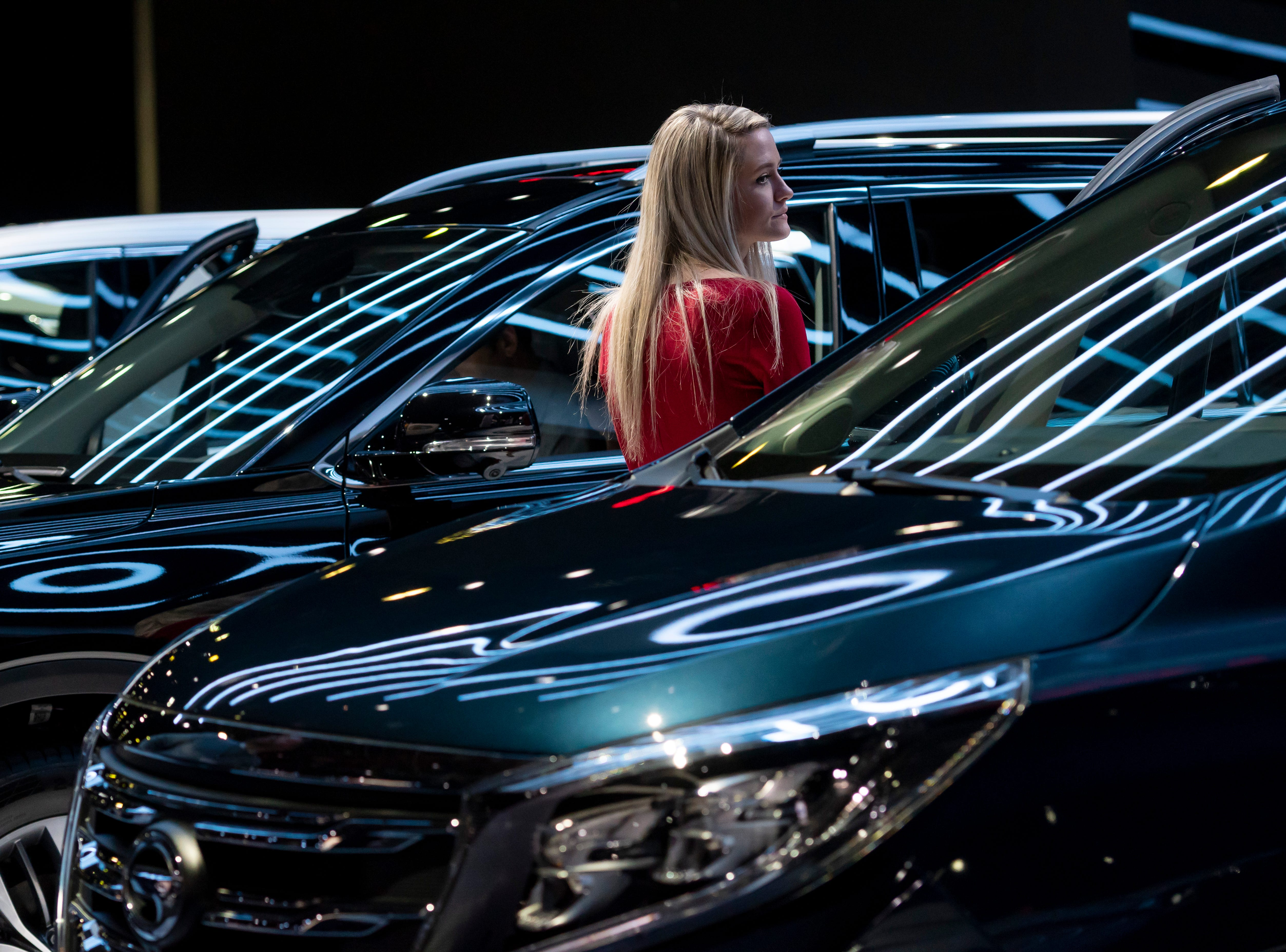 A spokeswoman stands among a row of vehicles at the GAC display.