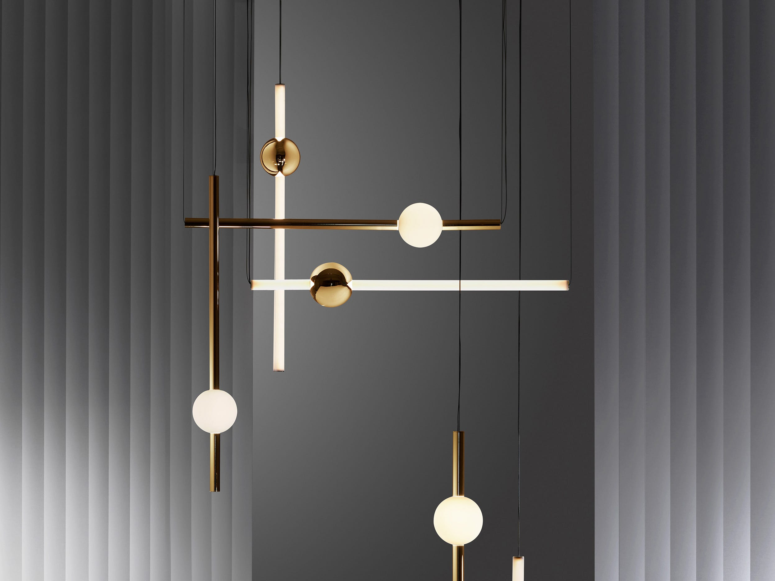 One of the U.K.'s leading product designers, Lee Broom, created a simple visual backdrop for his Observatory lighting installation. The Orion pendant set comprises simple modular tube lights with opposing opaque and solid polished gold spheres that connect and expand horizontally and vertically to create bespoke constellations of light.