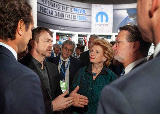 Fiat Chrysler Automobiles CEO Mike Manley speaks with U.S. Sens. Debbie Stabenow and Gary Peters, right, along with FCA Chairman John Elkann, far left, during the politicians' visit to the FCA exhibit space while touring the show floor at the North American International Auto Show in Detroit on Monday.