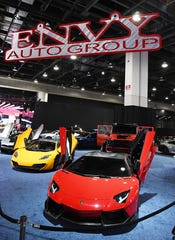 "A large area of the floor is now filled with customized luxury vehicles from the ""Envy Group"" at the North American International Auto Show."
