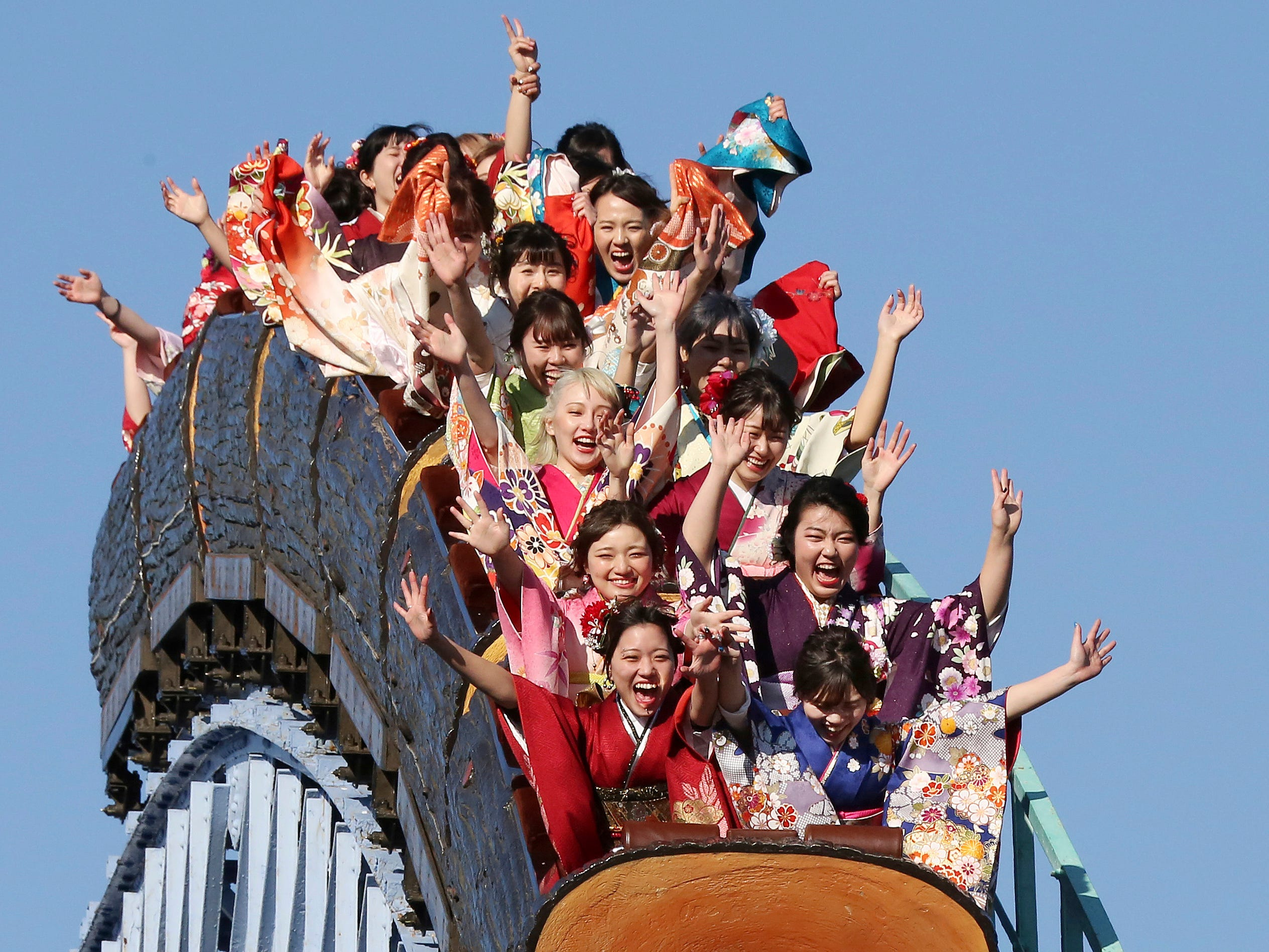 Kimono-clad women, who celebrate turning 20-years-old, react as they ride a roller coaster following a ceremony at Toshimaen amusement park on Coming of Age Day, a national holiday, in Tokyo, Monday, Jan. 14, 2019.