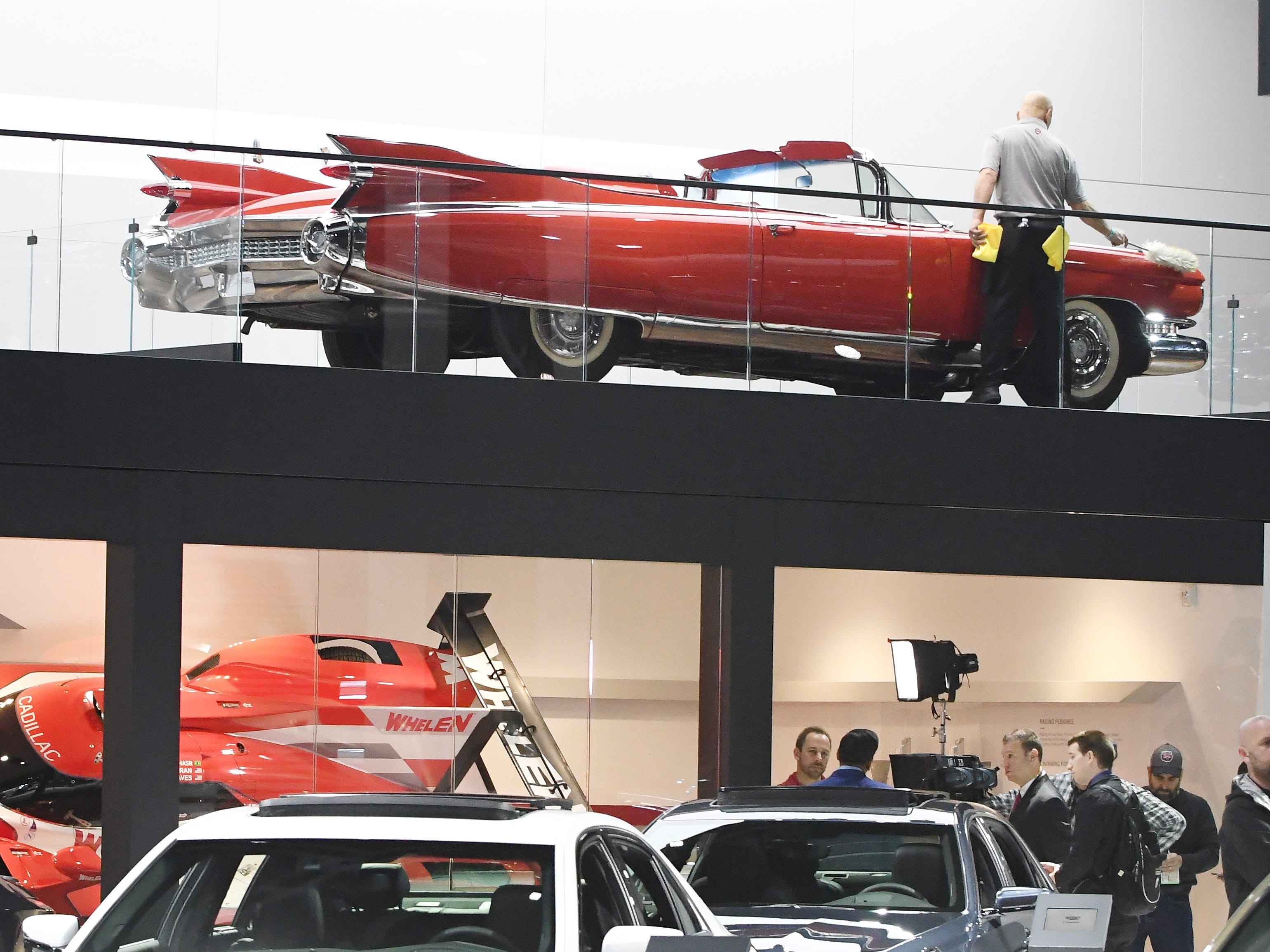 A worker dusts off a 1959 Eldorado in the Cadillac display.