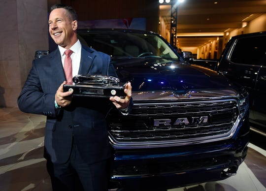 Reid Bigland, head of the Ram brand, shows off the Truck of the Year award next to the Ram 1500.