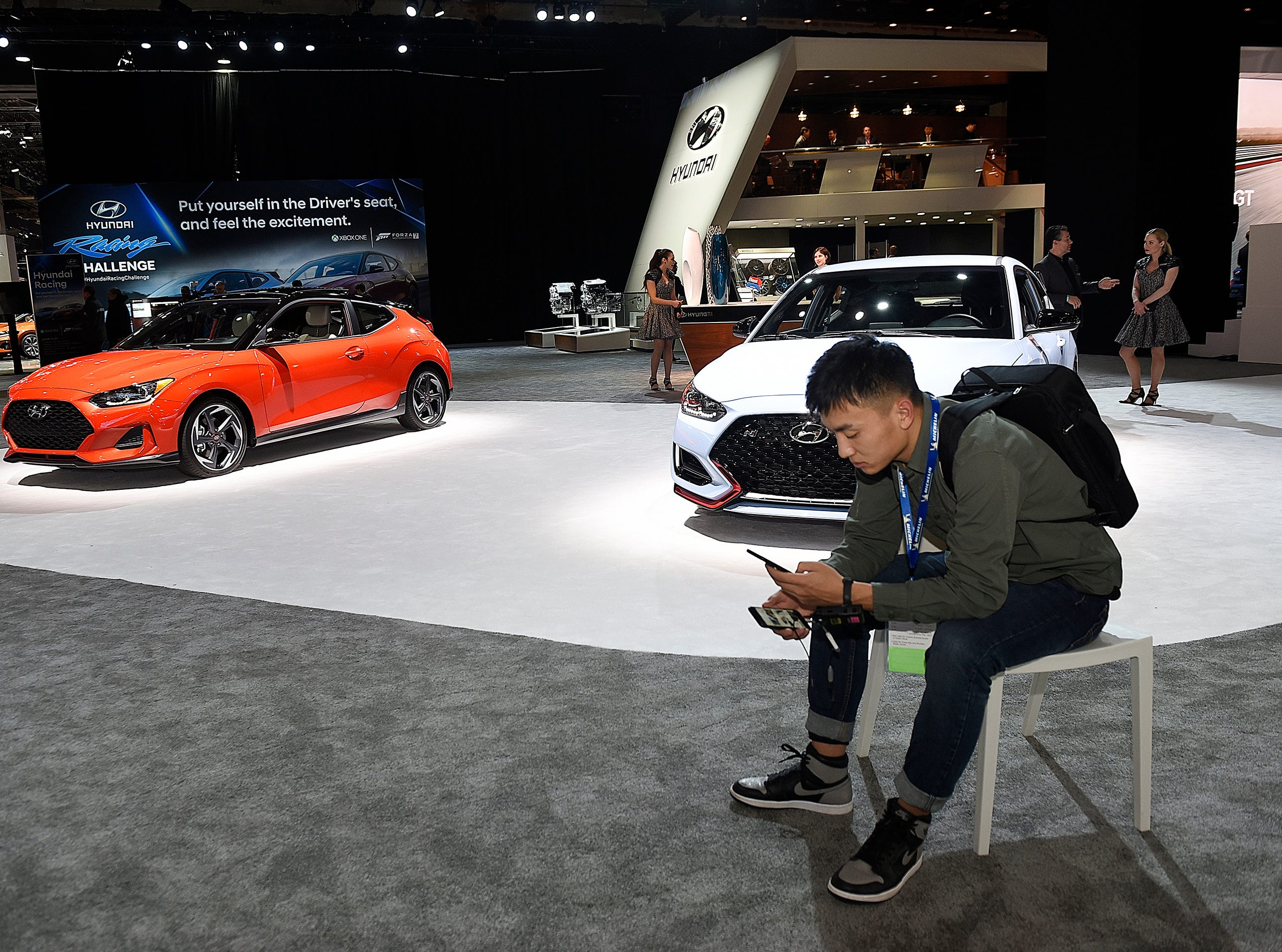 Journalist Zesong Guo, 25, of Autohome.com, Beijing, China, transfers photos from his phone inside the Hyundai exhibit.