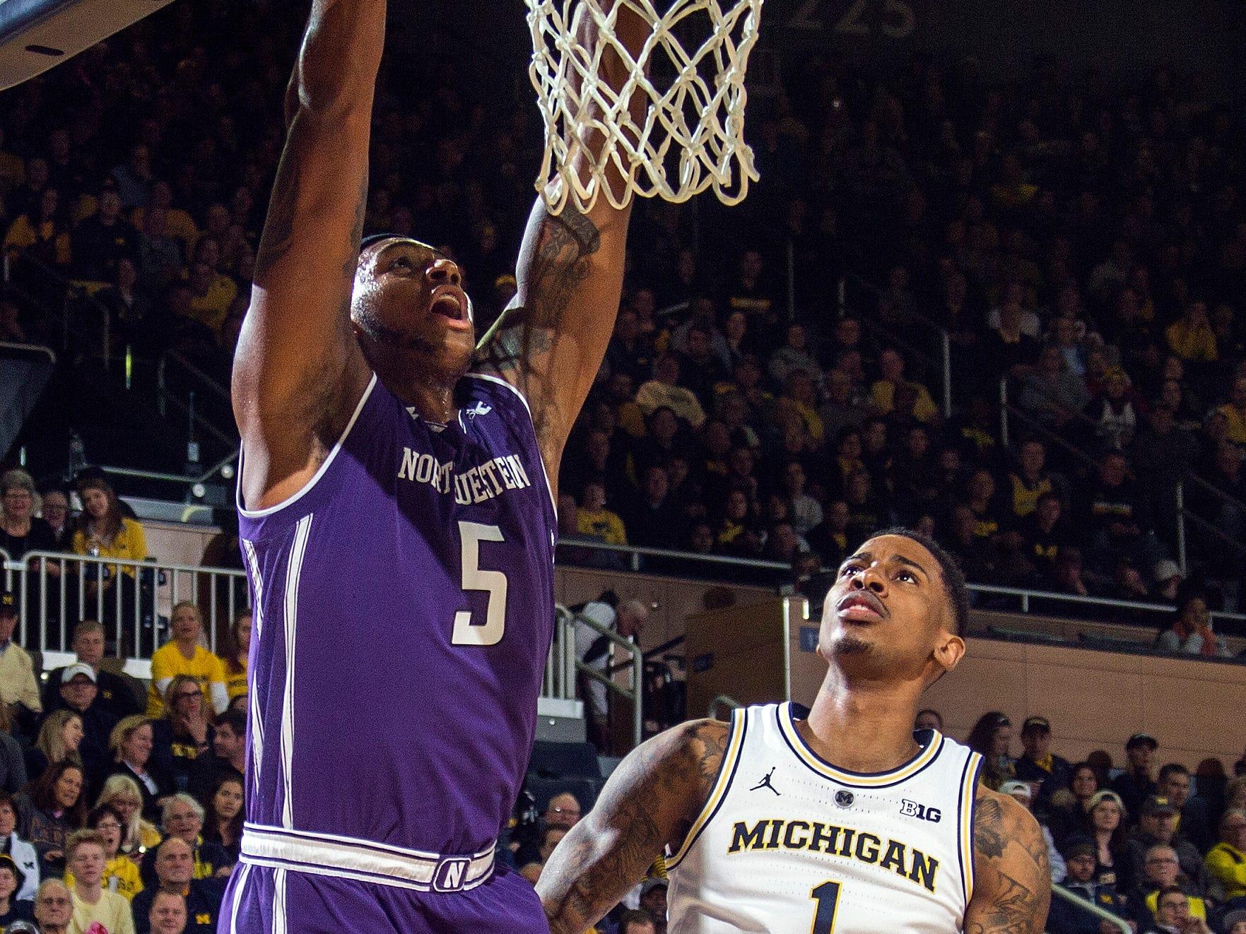 Northwestern center Dererk Pardon (5) dunks next to Michigan guard Charles Matthews (1) in the first half.