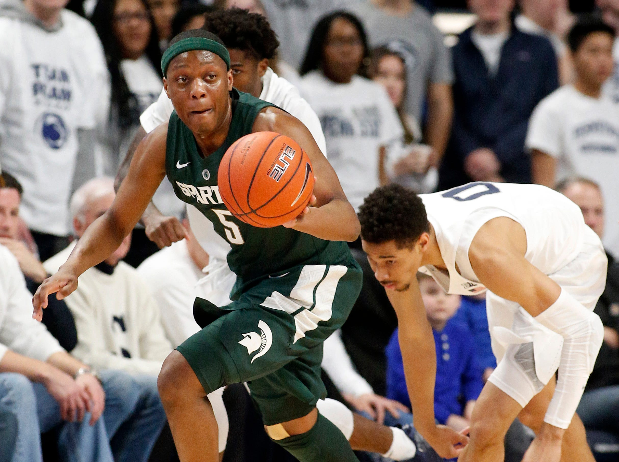 Michigan State's Cassius Winston (5) takes off with the ball after a steal against Penn State's Myreon Jones (0) during first half action of an NCAA college basketball game in State College, Pa. Sunday, Jan. 13, 2019. (AP Photo/Chris Knight)