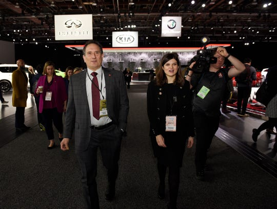 U.S. Reps. Andy Levin and Haley Stevens walk the show floor during Michigan's congressional delegation's tour of the auto show on Monday.
