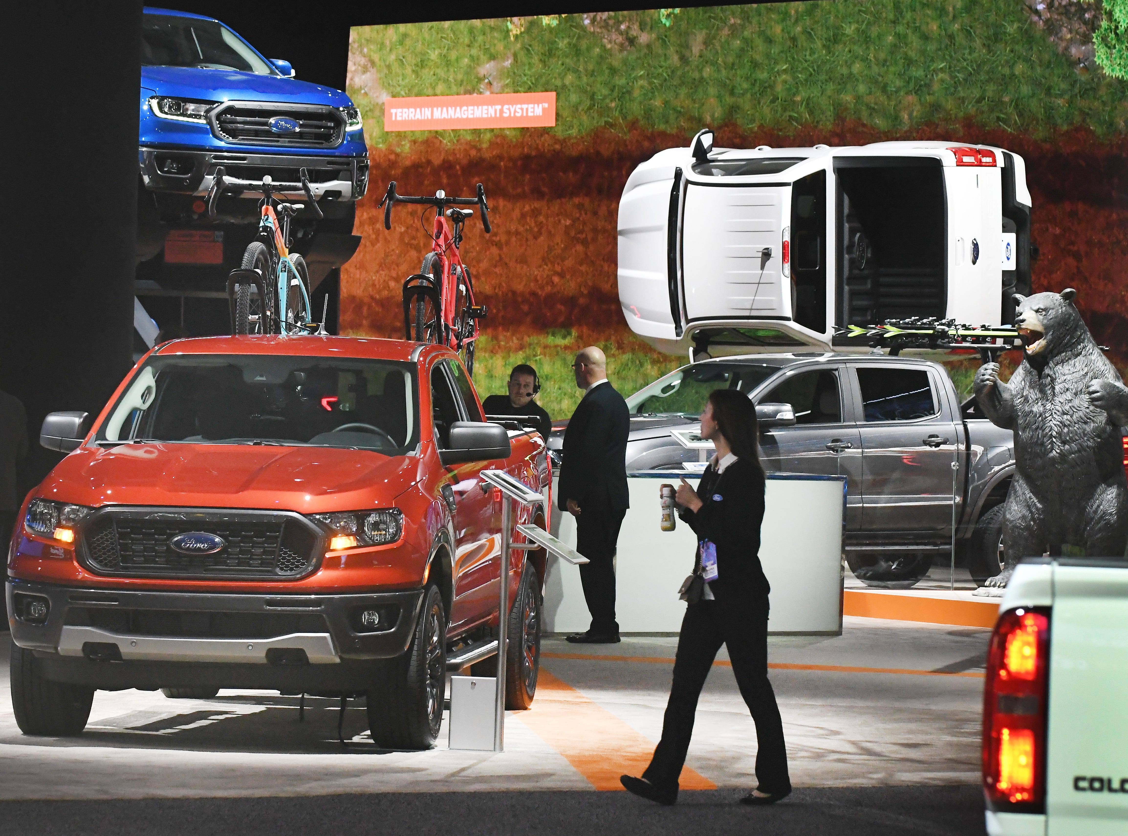Media members walk by the Ford exhibit at the North American International Auto Show at Cobo Center in Detroit on Monday, Jan. 14, 2019.