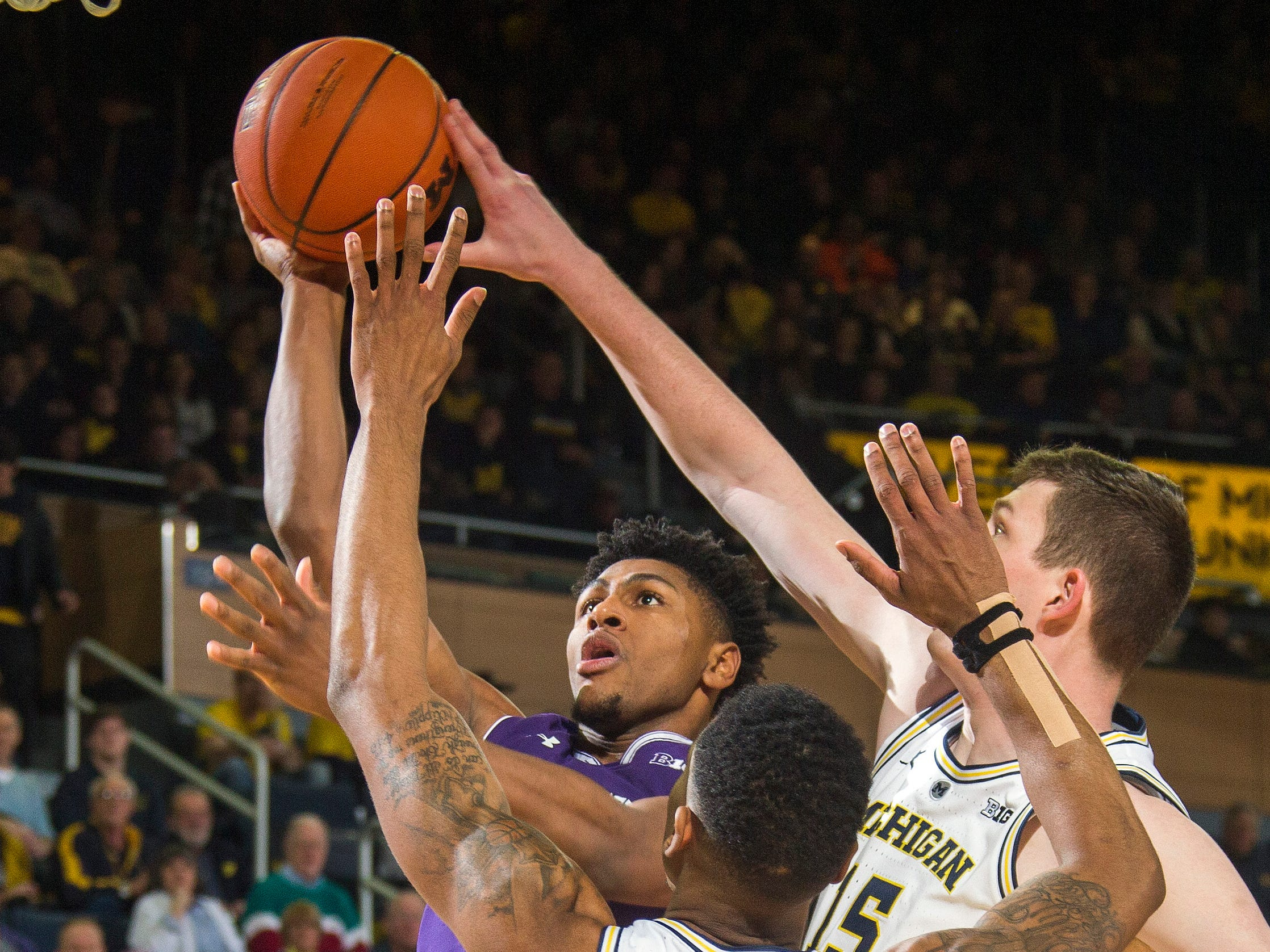 Northwestern guard Anthony Gaines, top left, goes to the basket while defended by Michigan guard Charles Matthews (1) and center Jon Teske, right, in the first half.