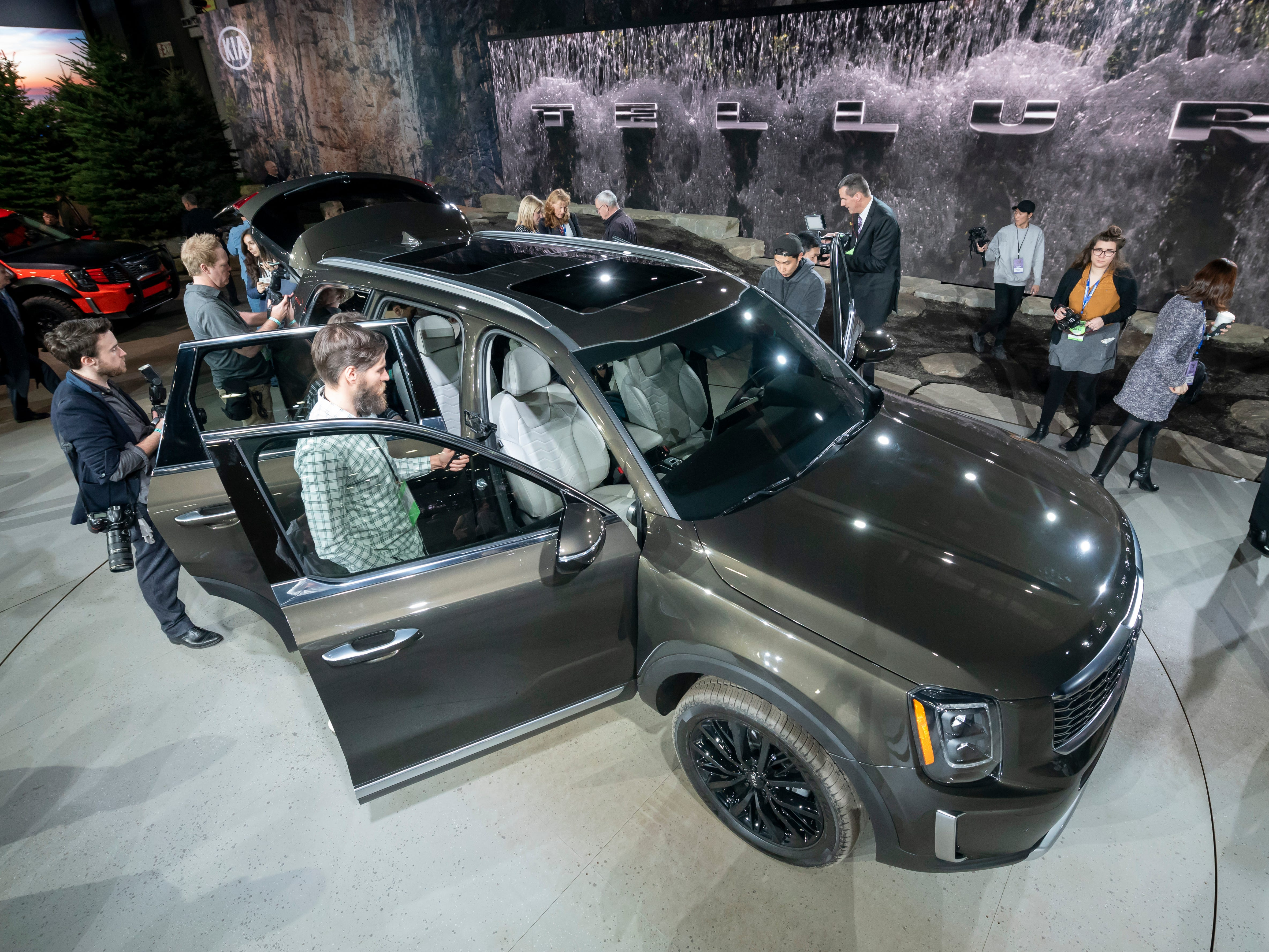 Journalists examine the 2020 Kia Telluride after its introduction.
