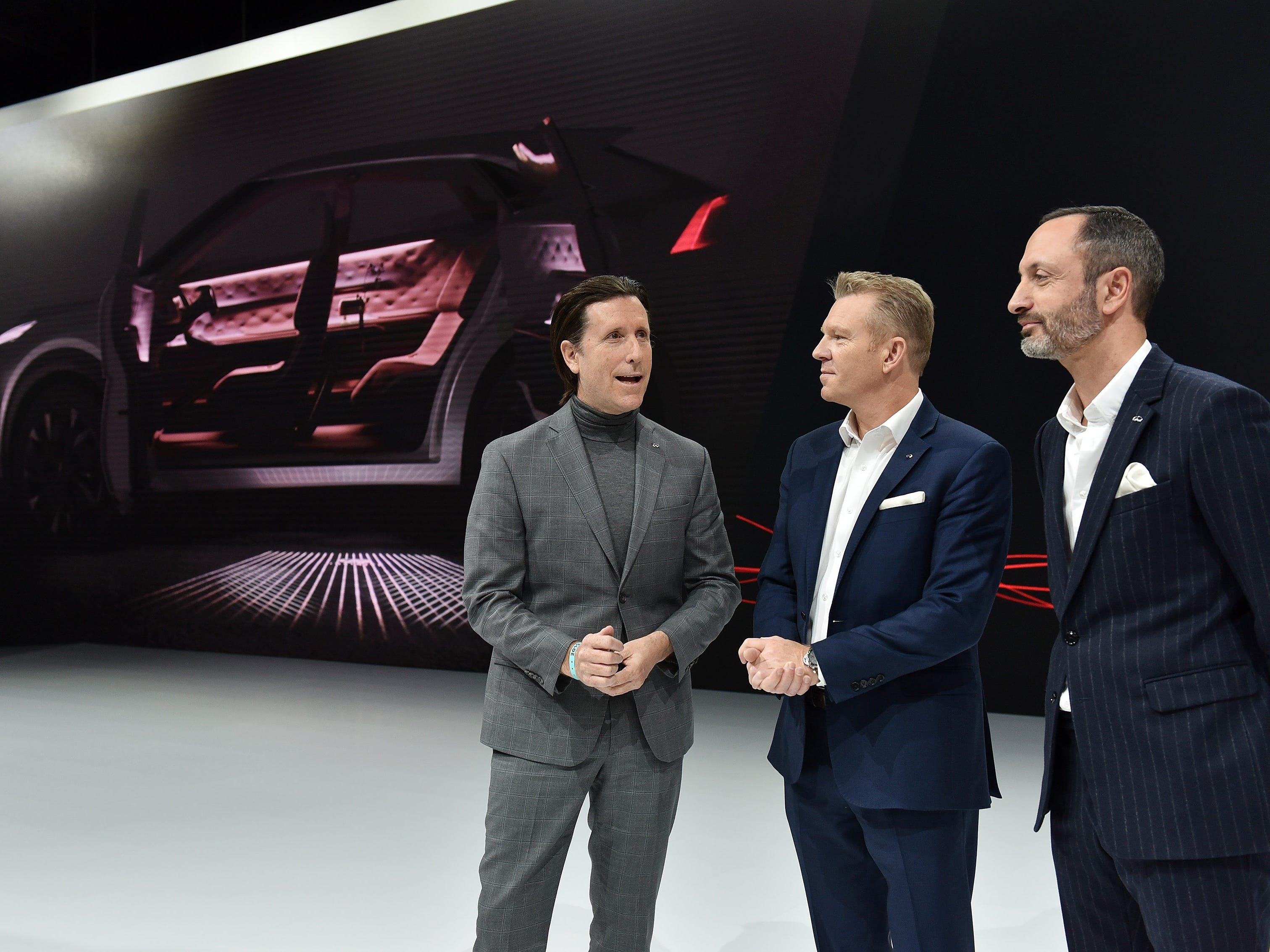 From left, Alfonso Albaisa, senior vice president of Global Design for Nissan Motor Co., Christian Meunier, chairman and president, Infiniti Motor Co., and Karim Habib, executive director of design, Inifiniti Motor Co., talk after their press event for the Infiniti QX Inspiration concept vehicle, which had technical issues and did not make it to the stage. The group took it all in stride and had the vehicle pushed onto the stage later Monday.