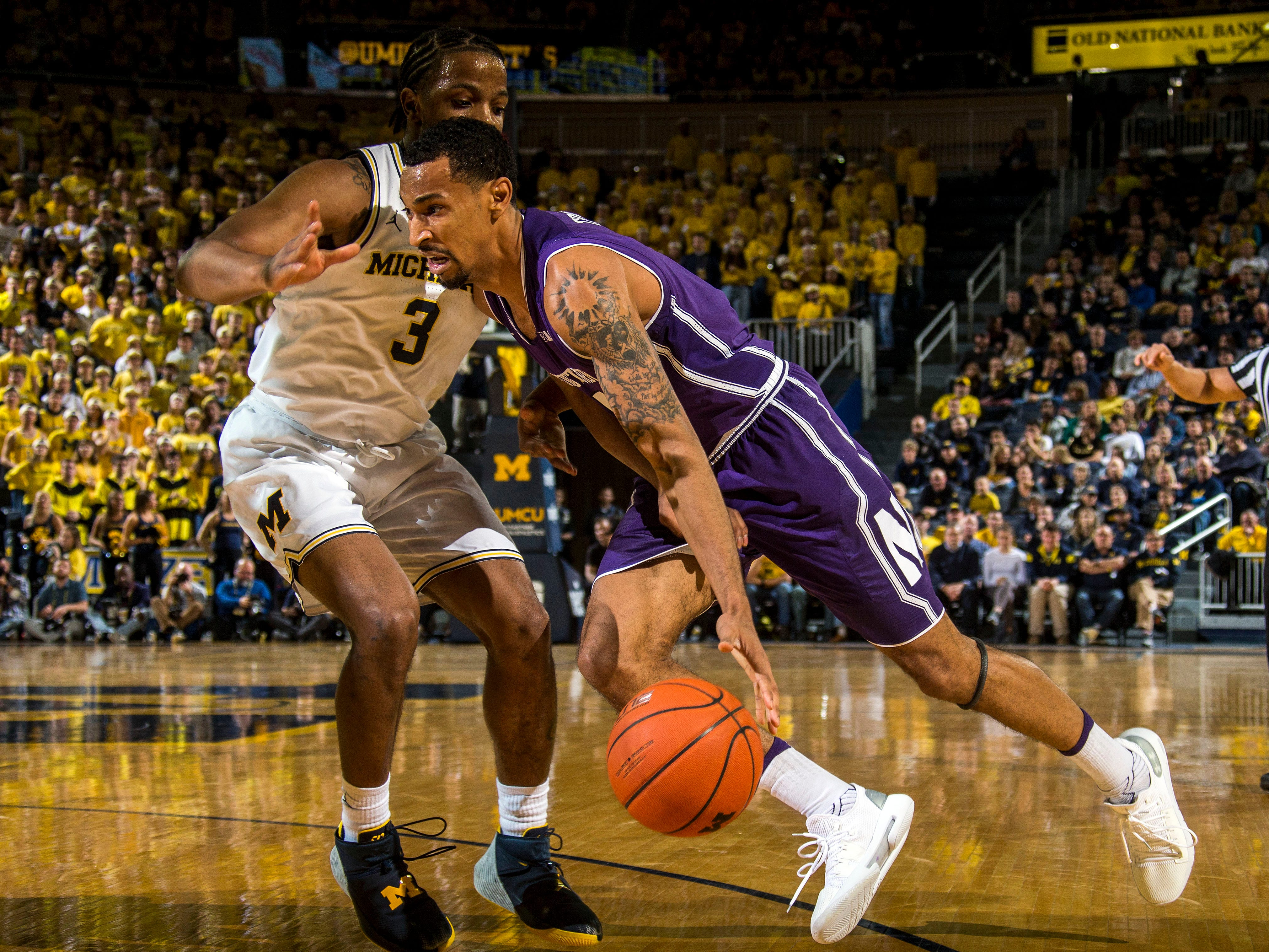 Northwestern guard Ryan Taylor, right, drives against Michigan guard Zavier Simpson (3) in the first half.