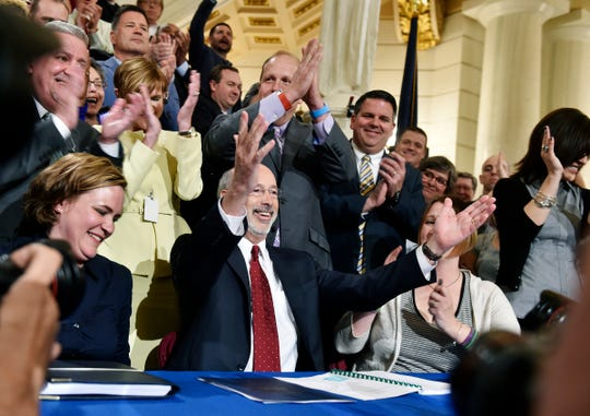 Pennsylvania Gov. Tom Wolf cheers after signing a bill April 17, 2016, to legalize a comprehensive medical marijuana program, at the Pennsylvania State Capitol Rotunda in Harrisburg.