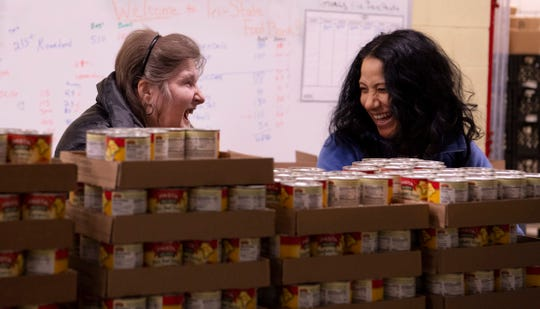 """Volunteers Lisa Davis, left, and Cecelia DePriest help out with the """"weekend backpacks"""" at the Tri-State Food Bank Monday afternoon. The food bank recipients may be in trouble if the organization isn't funded during the partial government shutdown."""