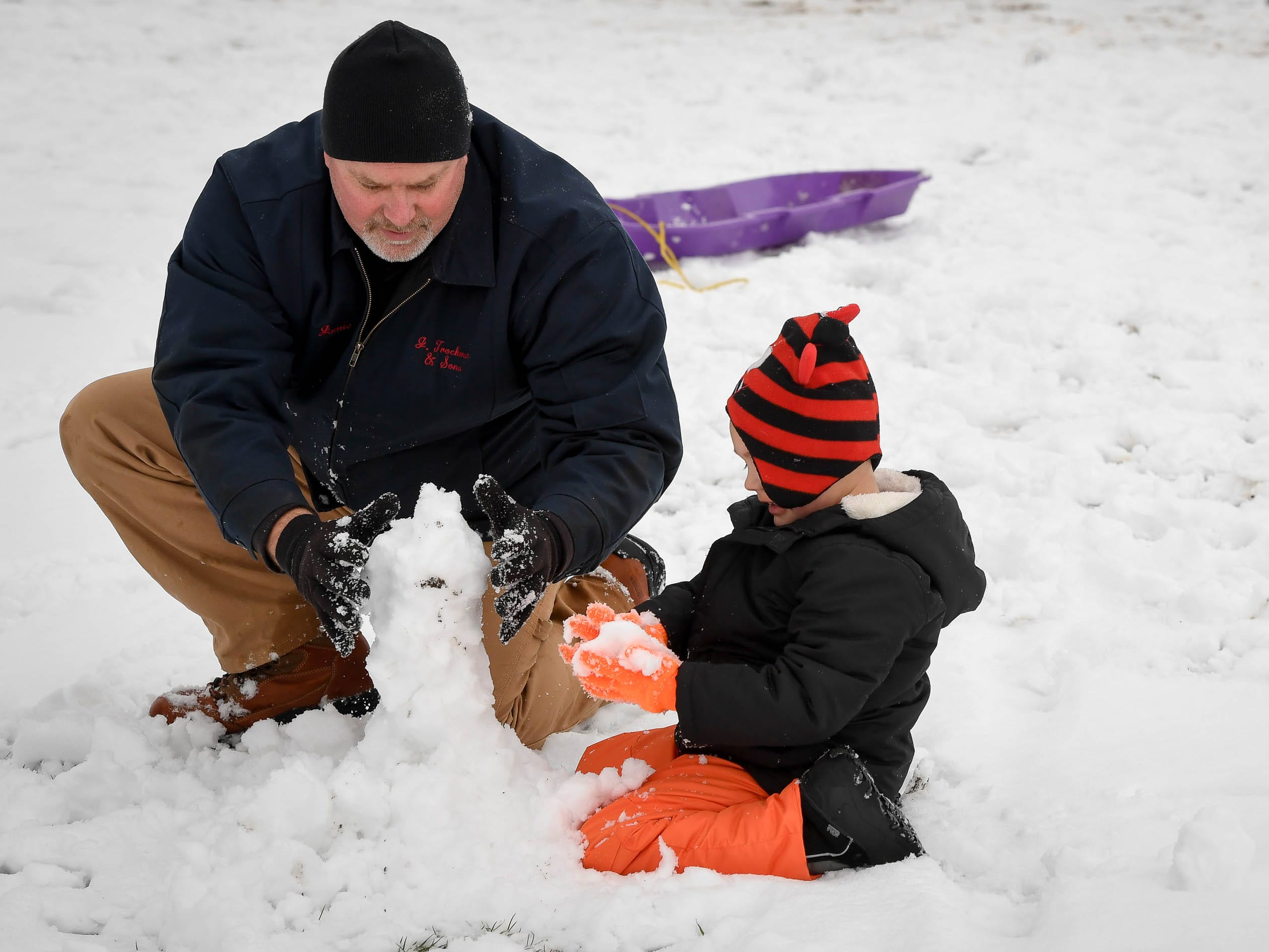 Using fresh snow from winter storm Gia, Jamie Harris, Henderson, builds a snowman with his grandson Gavin Cantley, five years-old, at Henderson's Municipal Golf Course Saturday, January 12 2019.