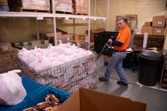 "Dennis Martin, Tri-State Food Bank volunteers supervisor, maneuvers a basket of 125 ""weekend backpacks"" from the assembly line Monday afternoon. The bags of food are given to area students on Fridays to keep them fed through the weekend."