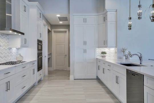 The kitchen has a pantry hidden behind the tall cabinet doors.
