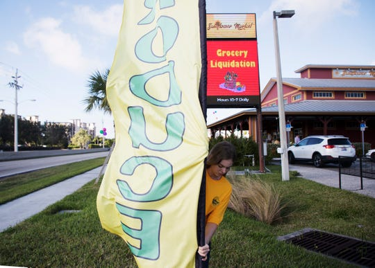 Brianna Crawford places a produce sign outside of the Sunflower Diacount Surplus Market on Hancock Bridge Parkway  in North Fort Myers on Monday.