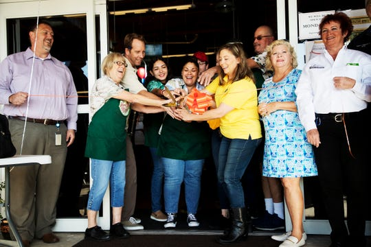Lisa Crawford, third from right, and her family including husband Paul, third from left, celebrate the ribbon cutting of their business, Sunflower Discount Surplus Market with members of the Cape Coral Chamber of Commerce and employees at the market on Hancock Bridge Parkway.