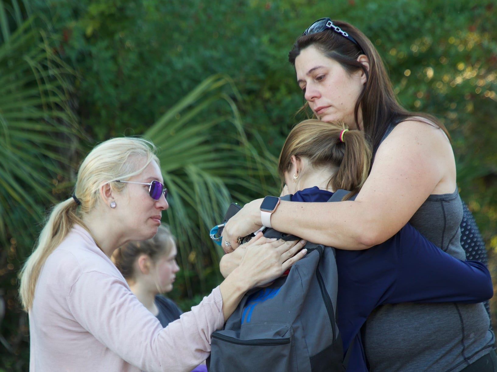 Skye Tamplin is comforted by family friends Kristen Lewis and Jessica Parke at the site where her sister Alana was killed by a driver on Durrance Road on Monday morning.
