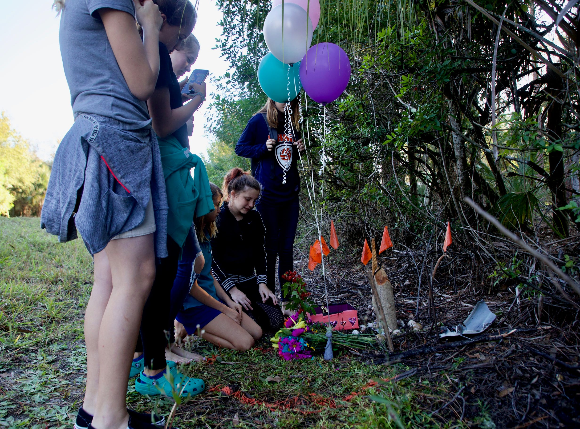 Family and friends of Alana Maria Tamplin, 12, including her sister Brooklynn, 9, kneeling and best friend Brooklyn Davis, also kneeling, pay their respects at a memorial site on Durrance Road. Tamplin was killed by a driver while walking home from a bus stop after dropping Brooklynn off. Her friend Brooklyn was also with her.