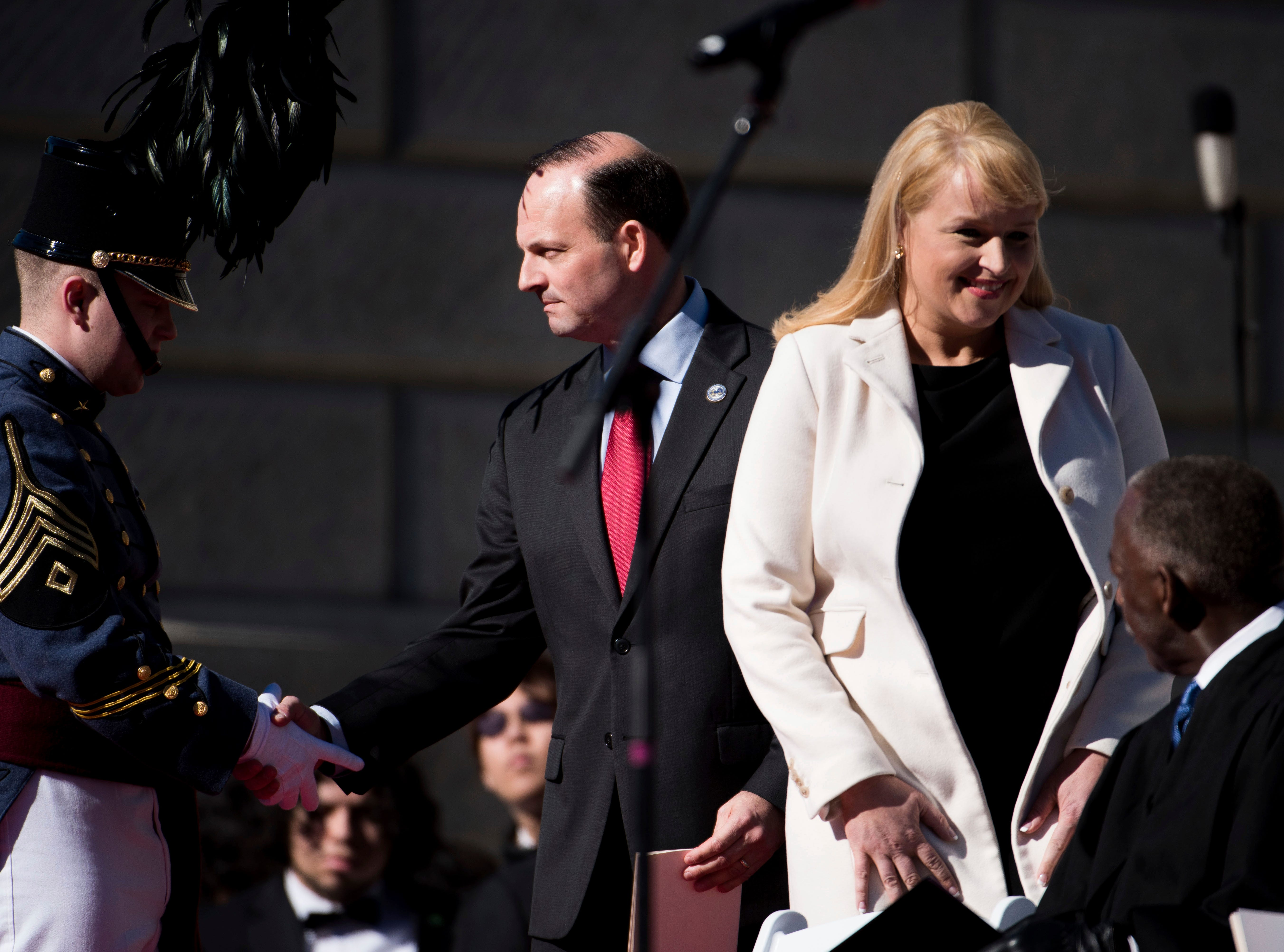 South Carolina Attorney General Alan Wilson, center, shakes the hand of a cadet from The Citadel as his wife, Jennifer Wilson, takes her seat during inauguration ceremonies for Governor Henry McMaster at the South Carolina Statehouse, Wednesday, Jan. 9, 2019, in Columbia, S.C. (AP Photo/Sean Rayford)