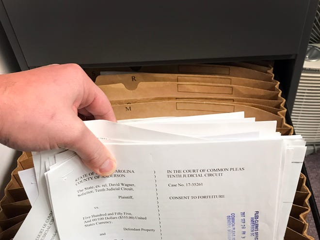 Reporter Mike Ellis photographs civil forfeiture documents stored in a cabinet at the Anderson County Courthouse. The TAKEN investigation discovered that these cases are never registered in court or assigned a case number.