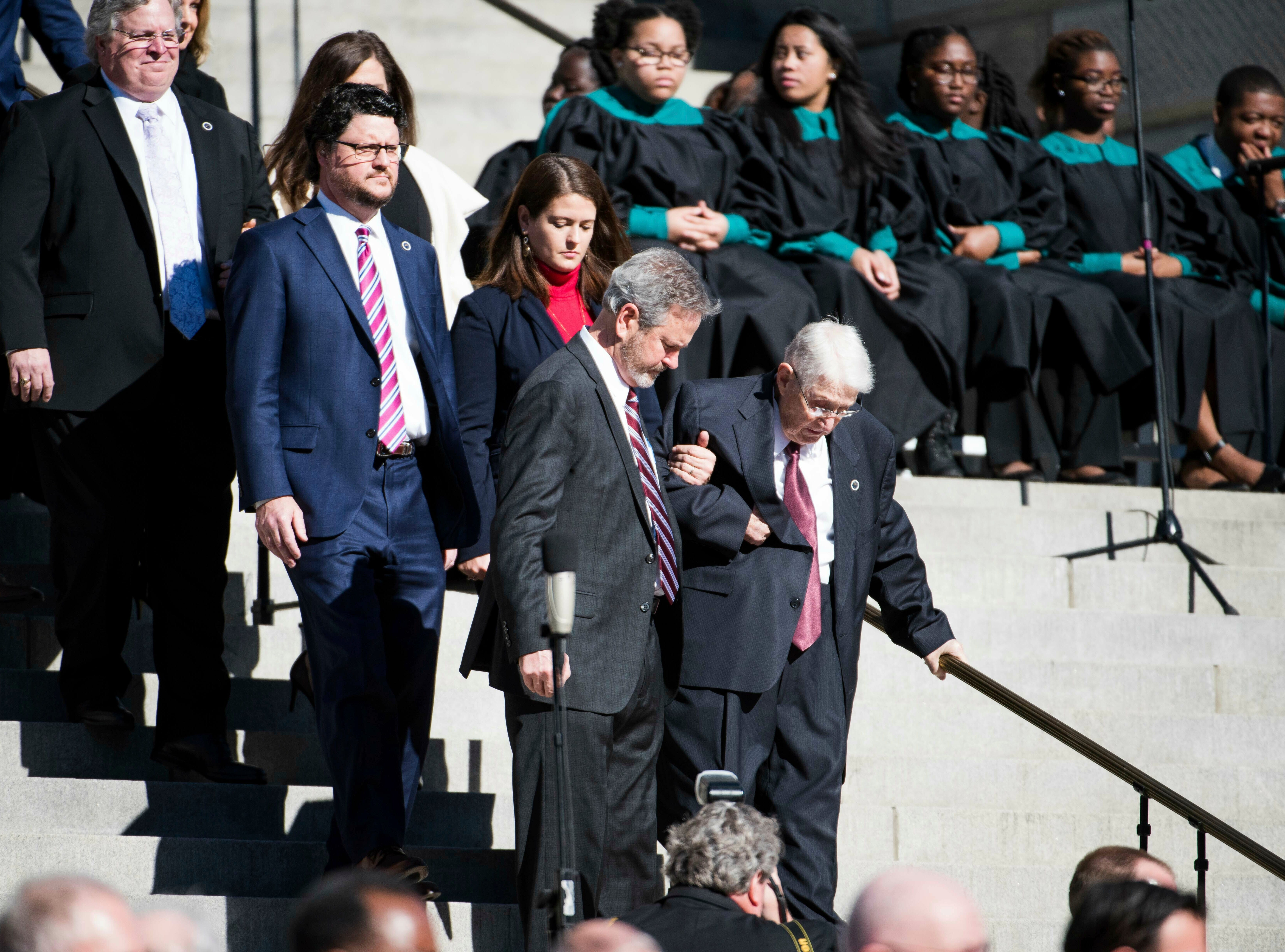 South Carolina House of Representatives Chaplin Charles Seastrunk, right, is helped down the steps at the South Carolina Statehouse as House Majority Rep. Gary Simrill, R-York, and his wife Mary Dobson, follow behind during inauguration ceremonies for Governor Henry McMaster, Wednesday, Jan. 9, 2019, in Columbia, S.C. (AP Photo/Sean Rayford)