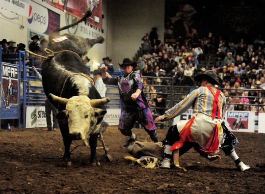 Bullfighters run to the aid of rider during the bull riding event at the Montana Pro Rodeo Circuit Finals in the Pacific Steel and Recycling Four Seasons Arena, Friday, January 11, 2019.