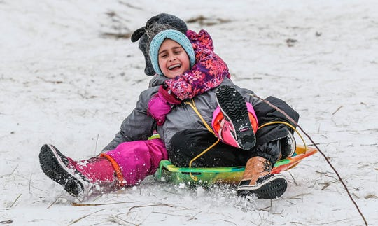 Alexis Harasty, front, and Lauren Quinto, rear, fly down the sledding hill at West Park in Carmel Ind. on Sunday, Jan. 13, 2019.