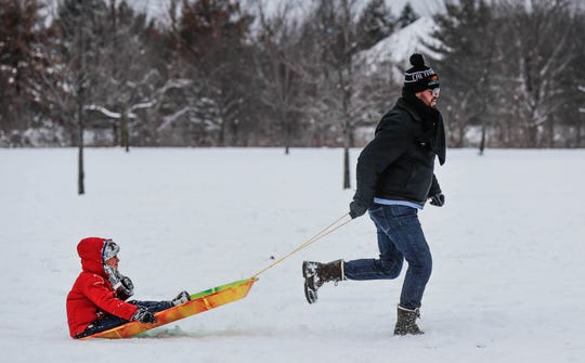 Luigi Castello pulls his son Phillip to the car after a day of sledding at West Park in Carmel Ind. on Sunday, Jan. 13, 2019.